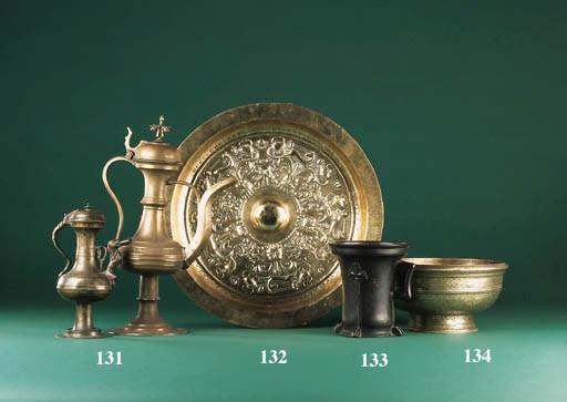 A circular brass alms dish