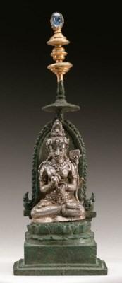 A silver figure of Tara on a b