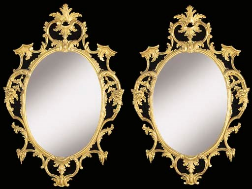 A pair of carved giltwood oval