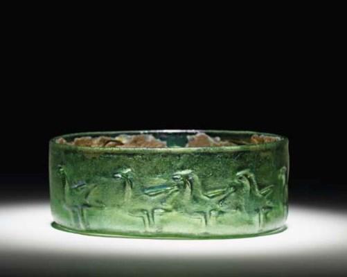 AN ISLAMIC GREEN GLASS BOWL WI