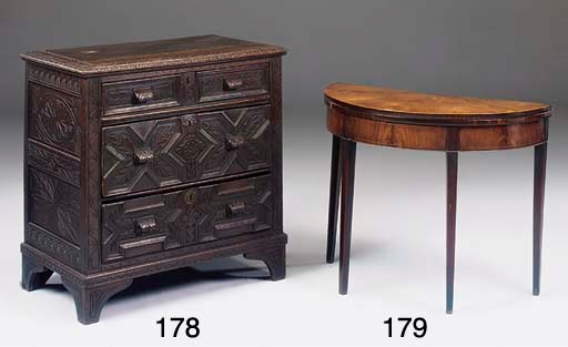 A CARVED OAK CHEST OF DRAWERS