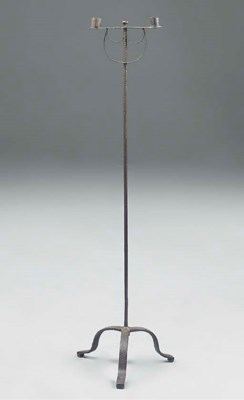 A wrought iron candlestick wit