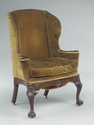 A CARVED WALNUT WING ARMCHAIR