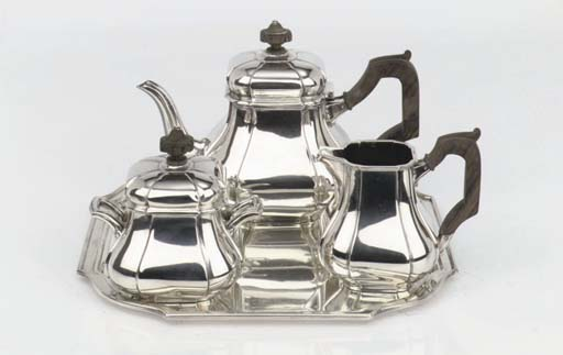 A Dutch silver three-piece tea service with a matched plated tray