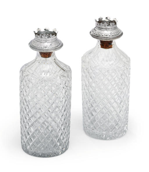 A PAIR OF VICTORIAN SILVER-MOUNTED STOPPERS WITH A PAIR OF CUT-GLASS DECANTERS