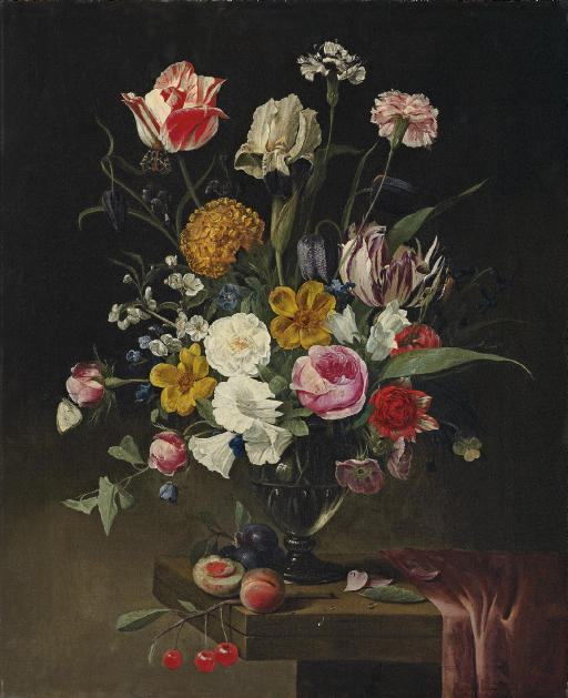 Roses, tulips, carnations and an iris in a glass vase on a draped stone ledge
