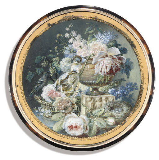 A still-life with white roses, a parrot tulip, white currents, corn flowers, stock, a camelia, lilac, a peonie and blue stock arranged in an urn set on a pedestal decorated with cherubs, a bird seated on the edge of a basket eating berries, and a nest with four blue eggs