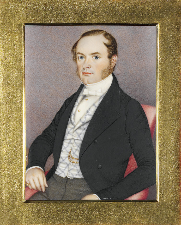 James Samuel Hartley, in black coat, blue patterned white waistcoat, white shirt with gold buttons, white bow tie, grey trousers, seated in red upholstered chair, his right elbow leaning on a desk