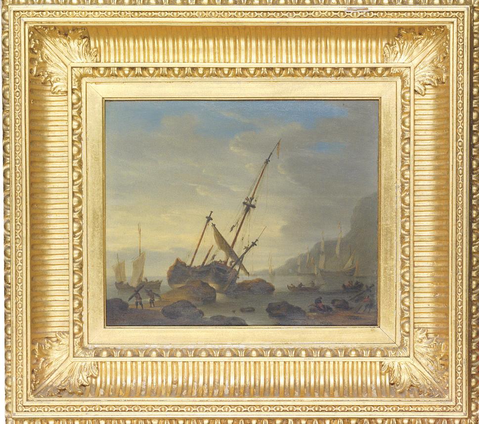 A coastal landscape with a sailing ship run aground