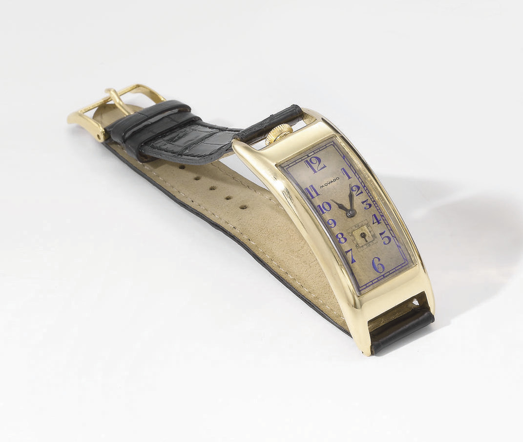Movado. An unusual, large and early 18K gold rectangular curved hinged wristwatch