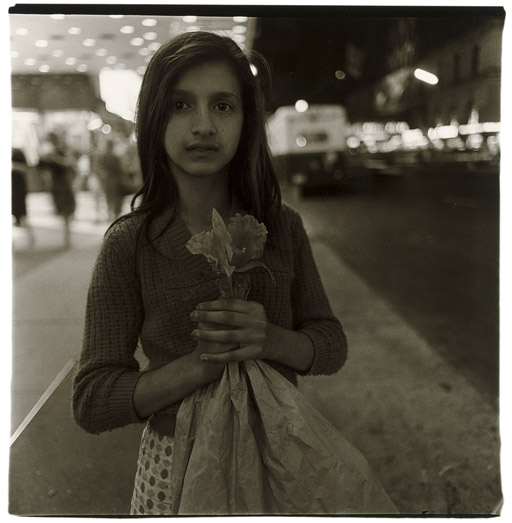 Child selling plastic orchids at night, N.Y.C. 1963