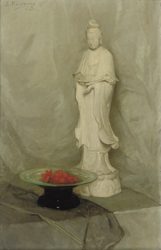 A Guanyin statue and a bowl with red flowers on a table