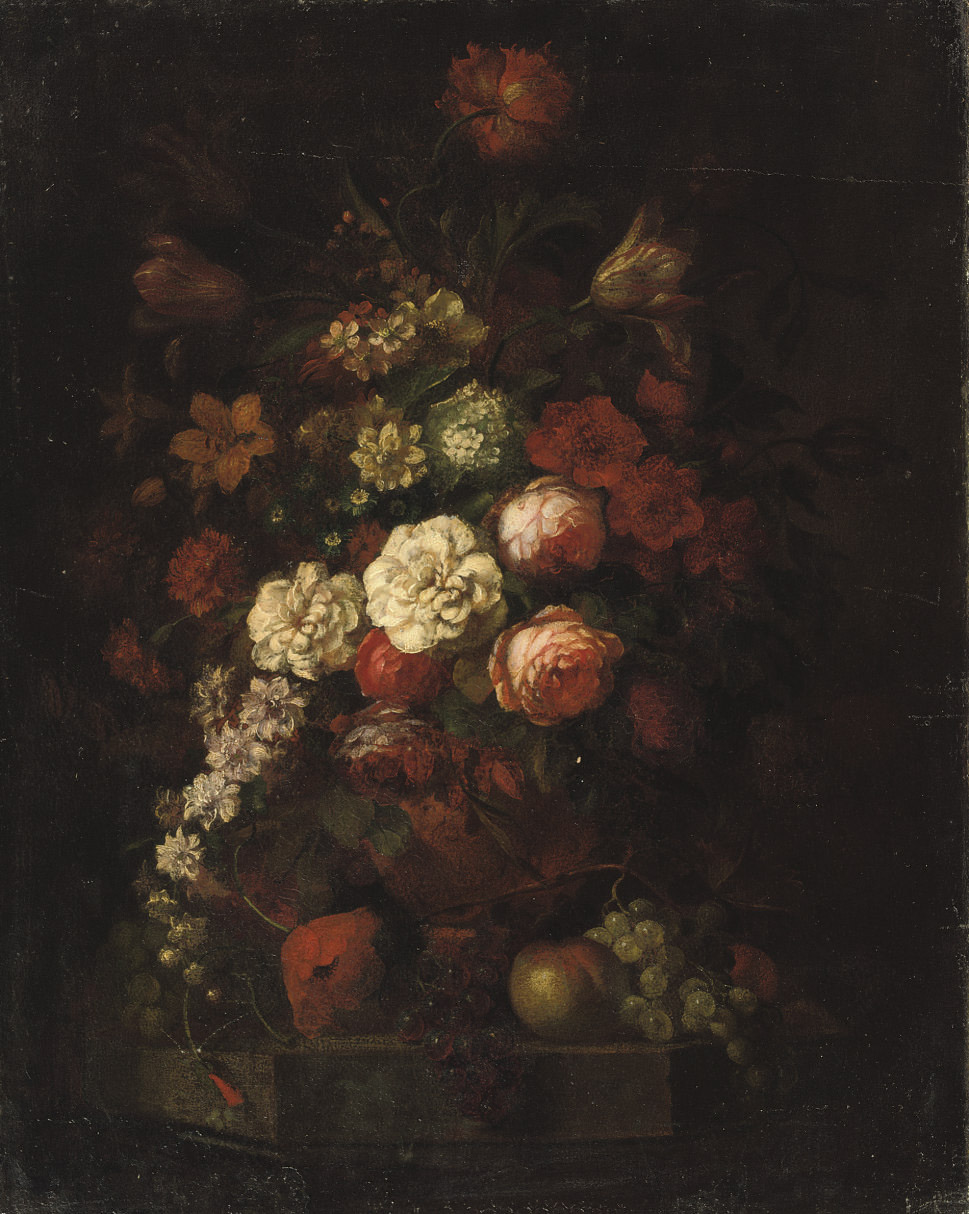 Pink roses, tulips and various other flowers in a vase together with red and blue grapes and apples on a ledge