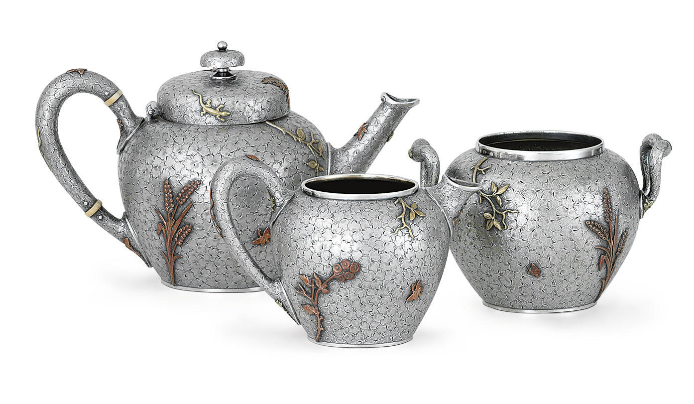 A THREE-PIECE SILVER AND MIXED-METAL TEA SERVICE**