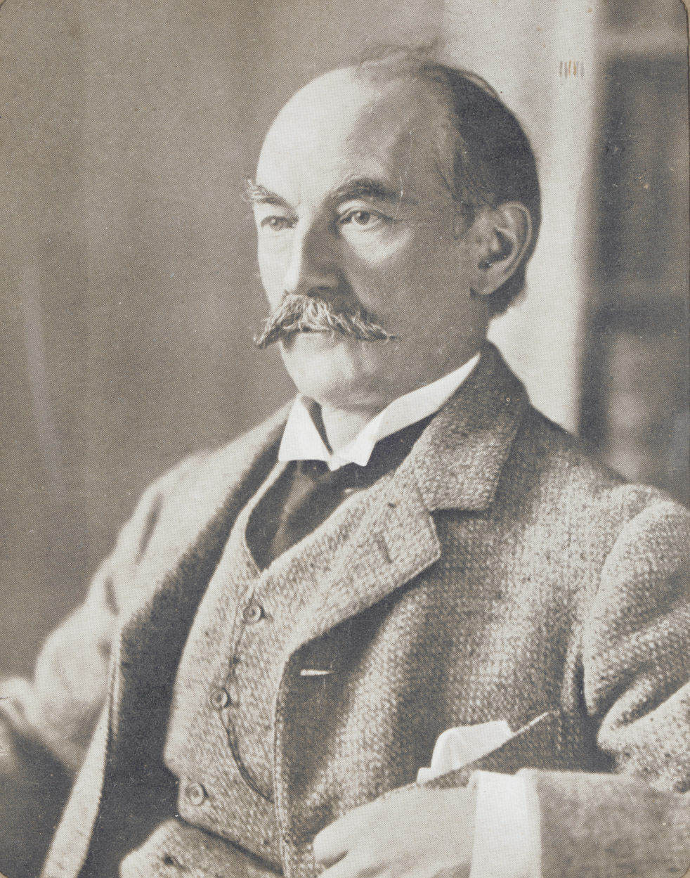 HARDY, Thomas (1840-1928). Photograph signed (on mount, 'Thomas Hardy'), a half-length portrait showing the author seated, in a tweed suit, [c.1890], half-tone print, 116 x 92mm, in a mount 175 x 147mm, framed and glazed.