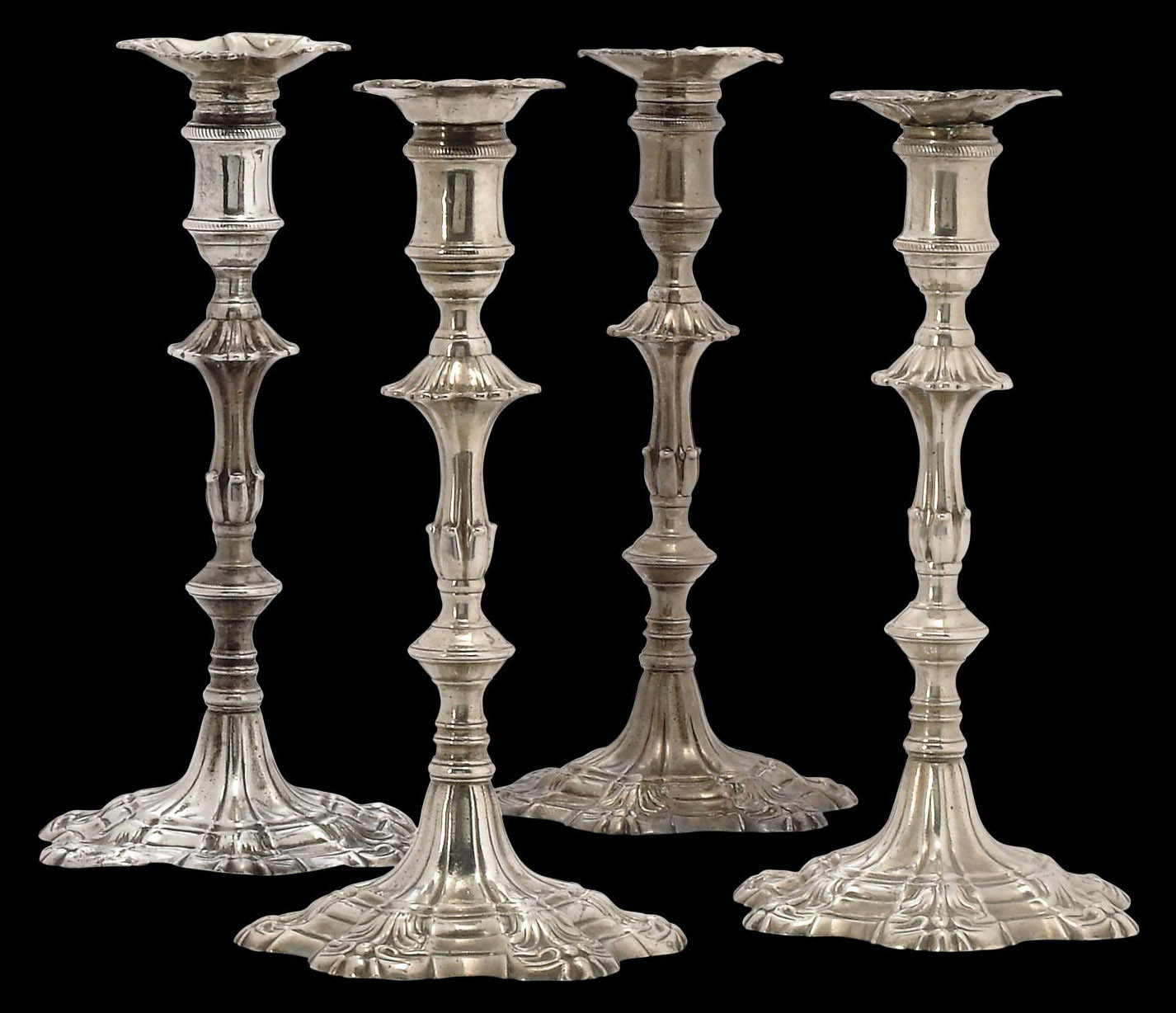 A SET OF FOUR GEORGE III CAST SILVER CANDLESTICKS