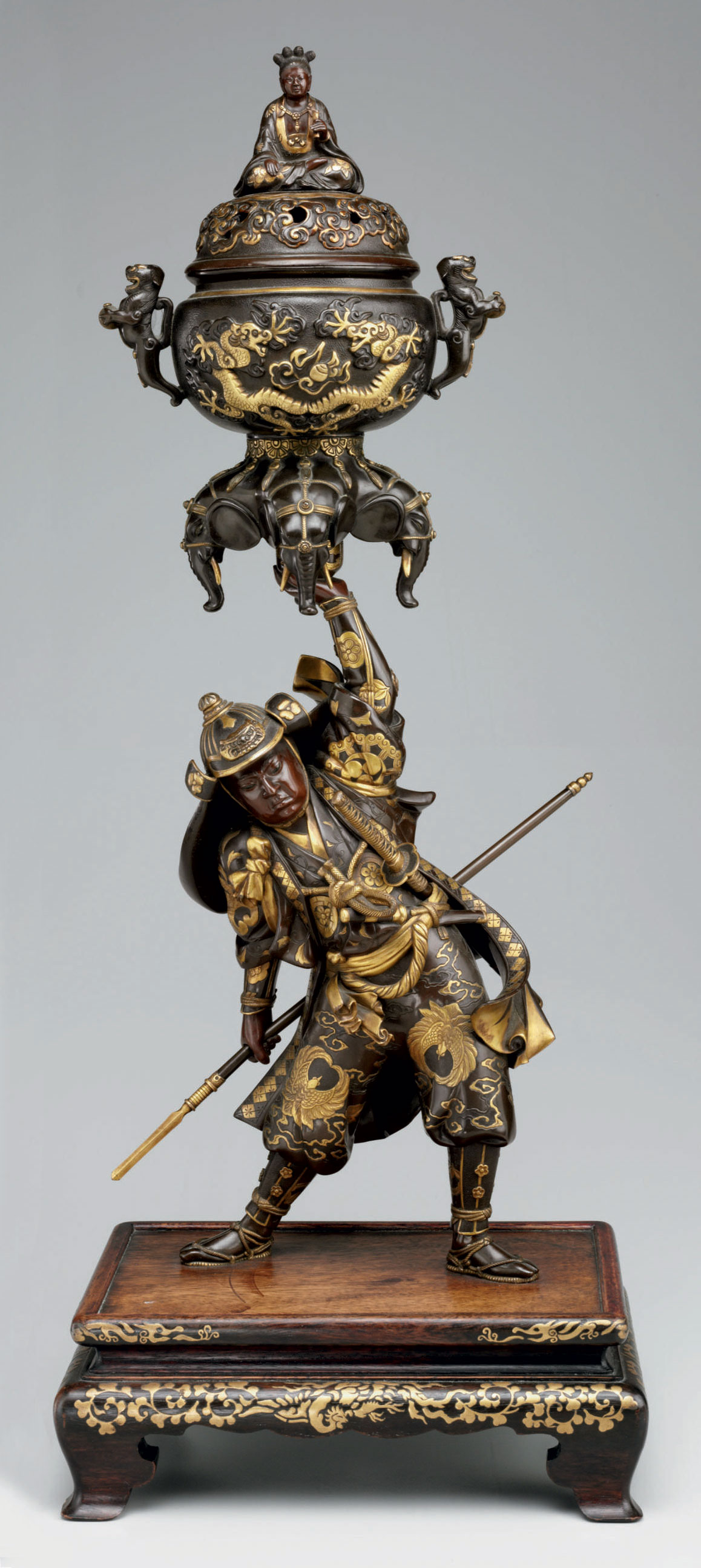 An inlaid-bronze figural incense burner