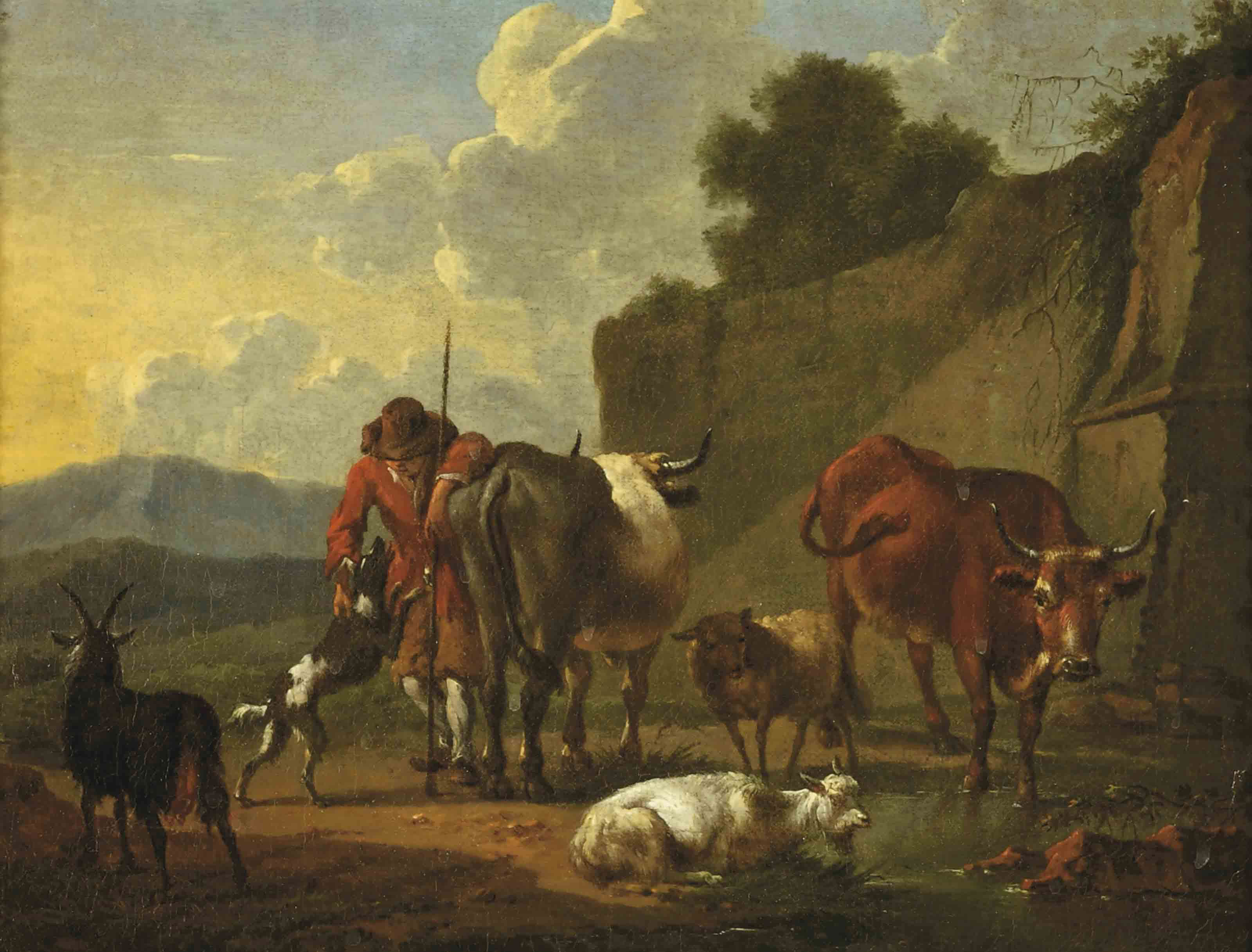 A herdsman with his cattle resting near a stream