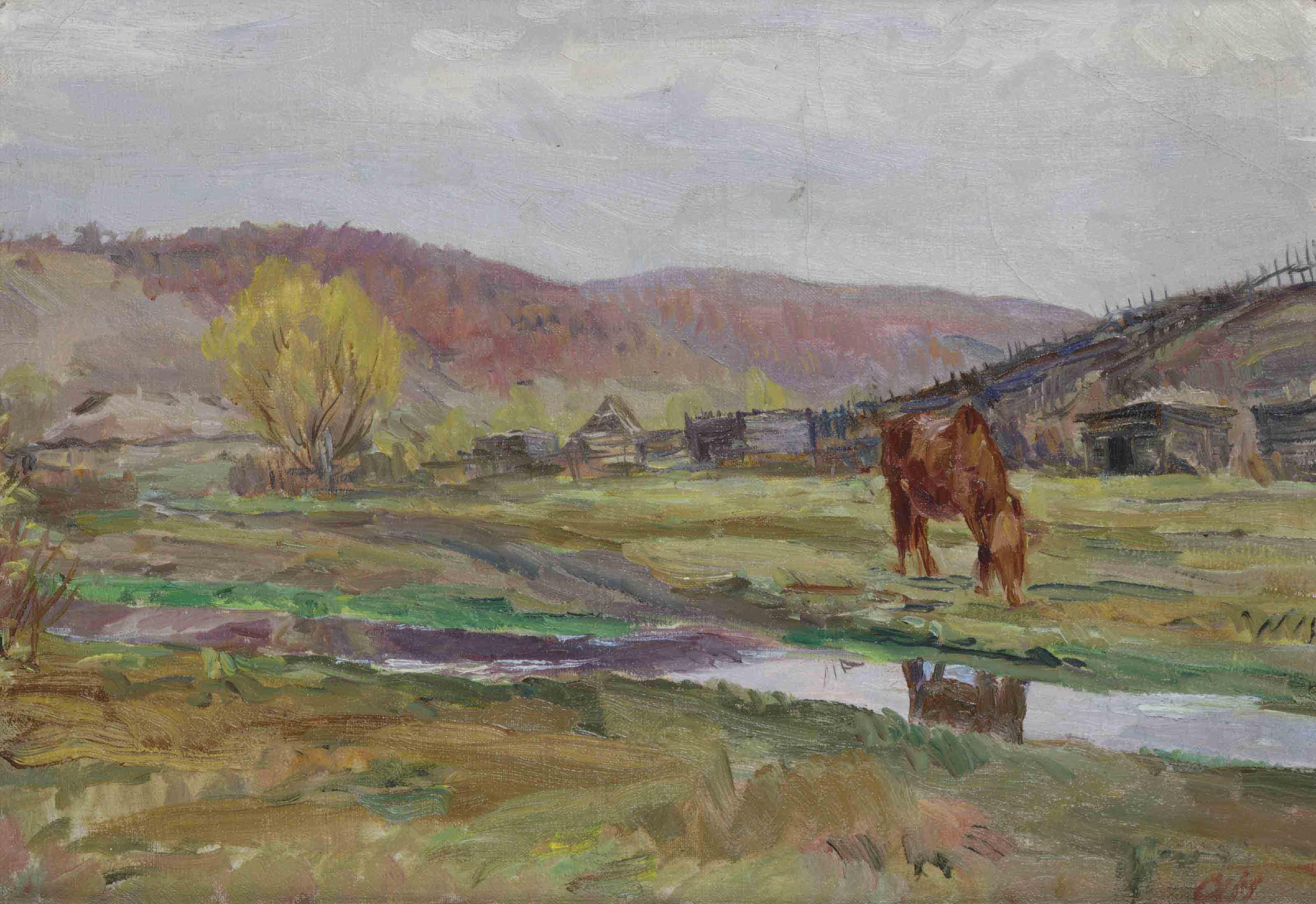 A horse grazing in a field along a river