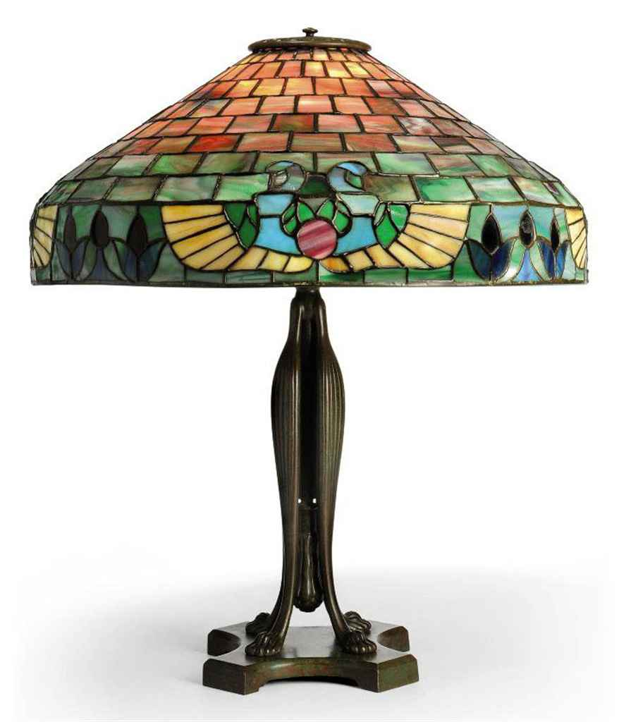 A HANDEL 'EGYPTIAN' PATTERN LEADED GLASS SHADE ON A TIFFANY STUDIOS PATINATED BRONZE 'TELESCOPIC' BASE