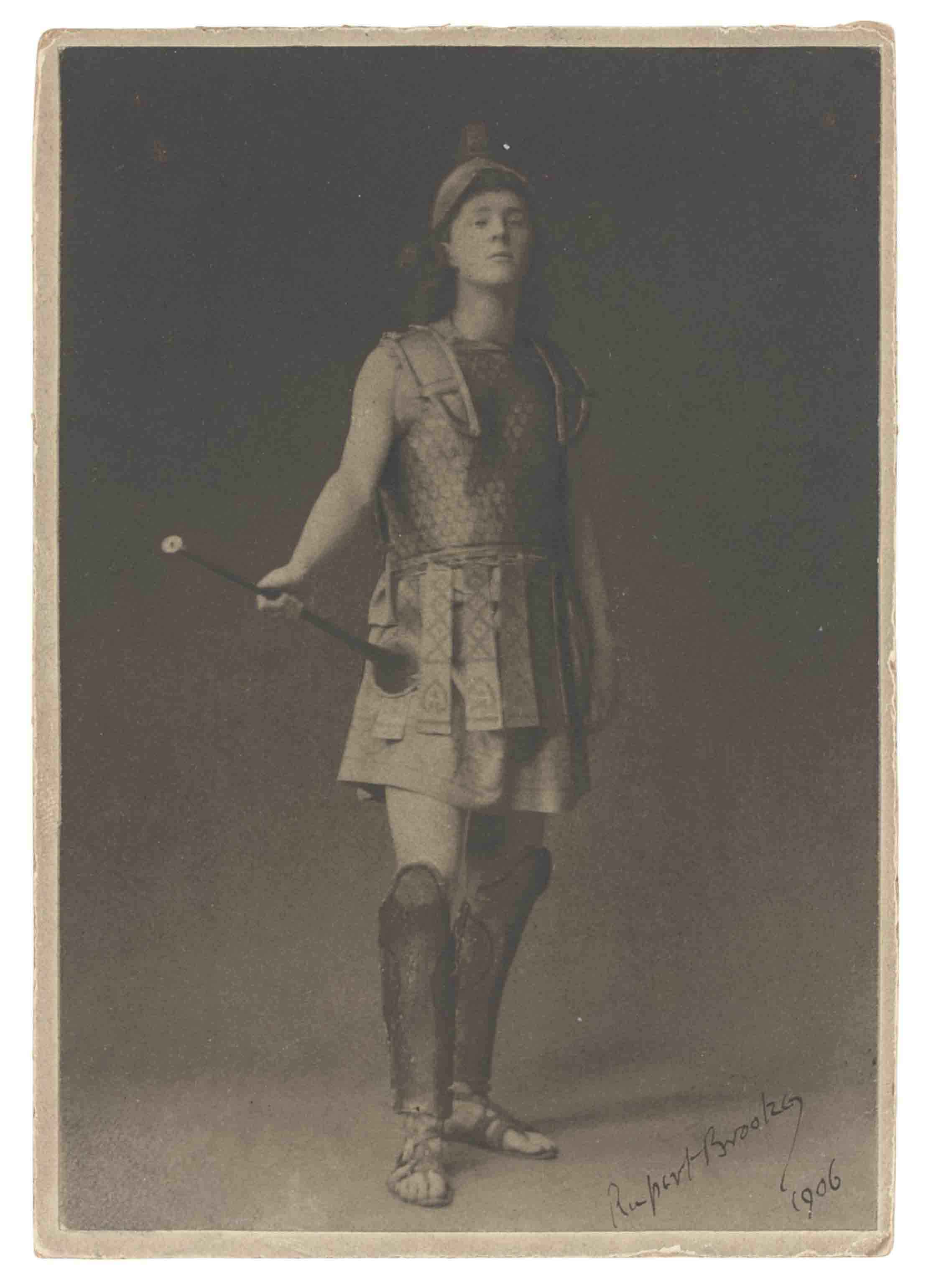BROOKE, Rupert (1887-1915). Portrait photograph signed ('Rupert Brooke  1906') showing Brooke in costume as the herald in Aeschylus's Eumenides, image 144 x 99mm, mount 150 x 105mm, envelope. Provenance: Roger Senhouse collection (his notes to verso, identified in catalogue excerpt from an unidentified sale).