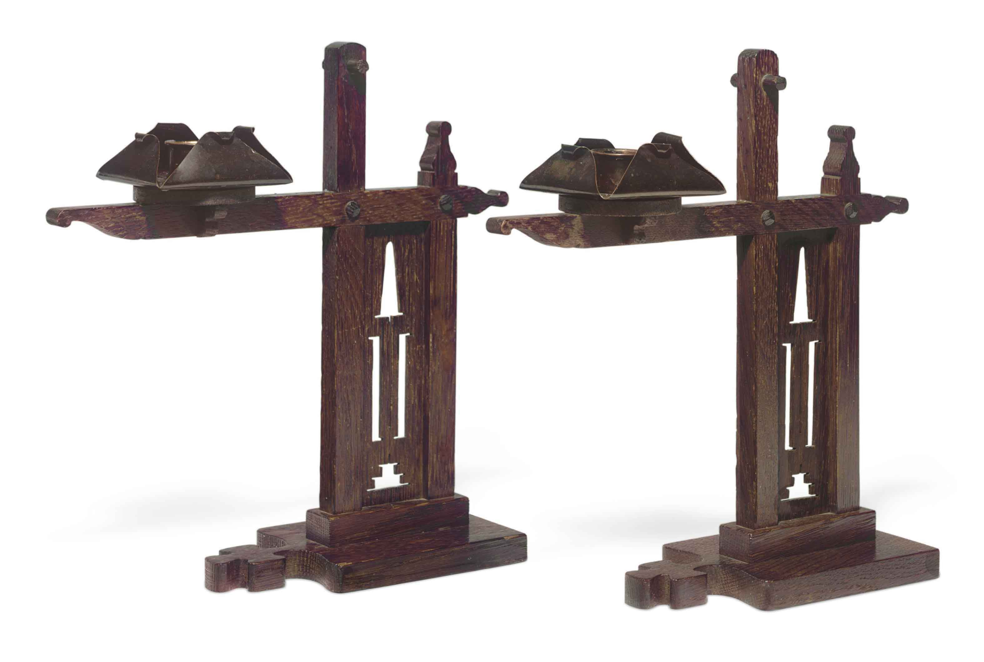 A PAIR OF ARTS AND CRAFTS OAK AND COPPER 'CRESSET' CANDLESTICKS,