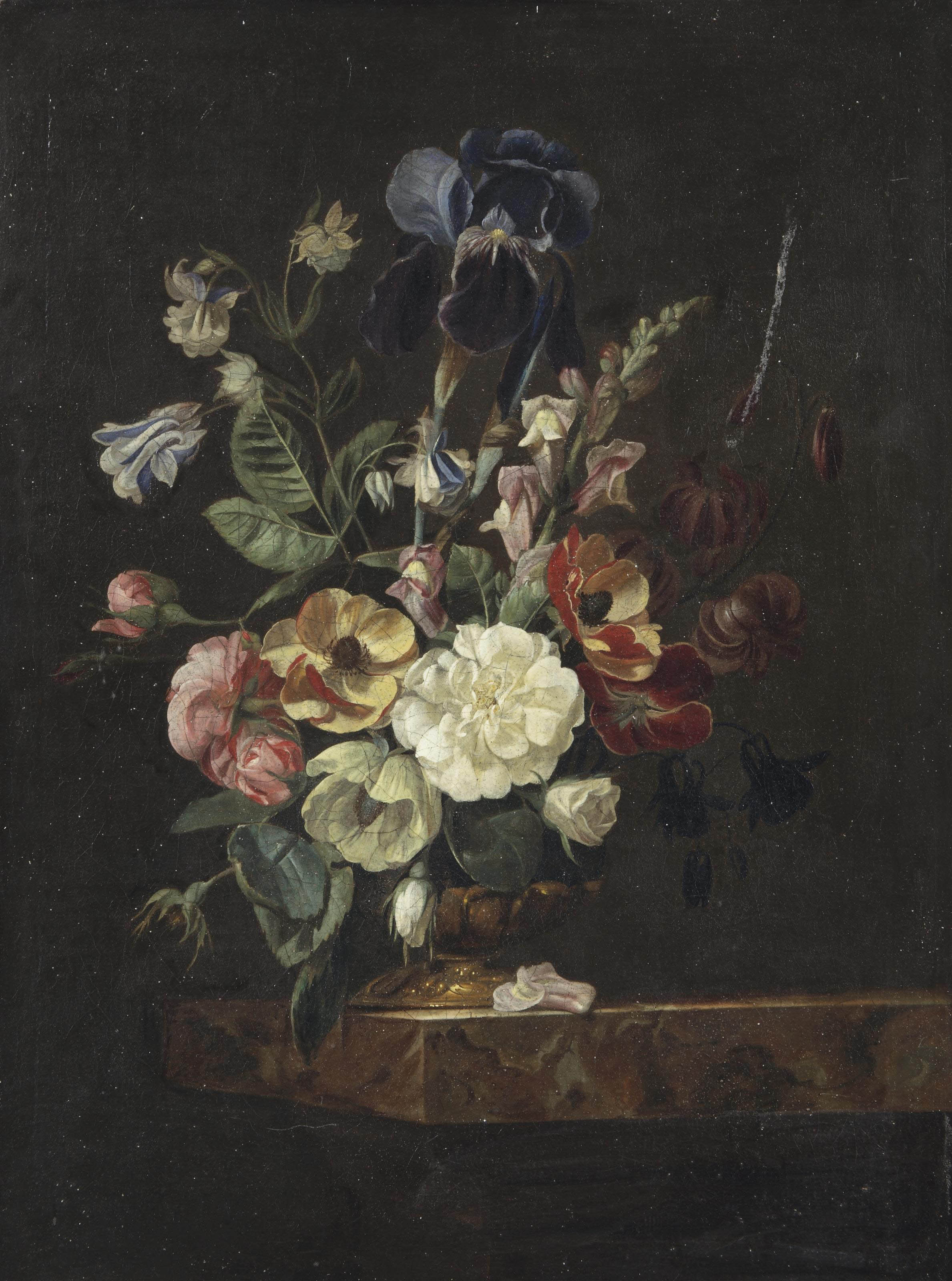 Carnations, blue morning glory, peony, irises and various other flowers in a golden vase on a marble ledge