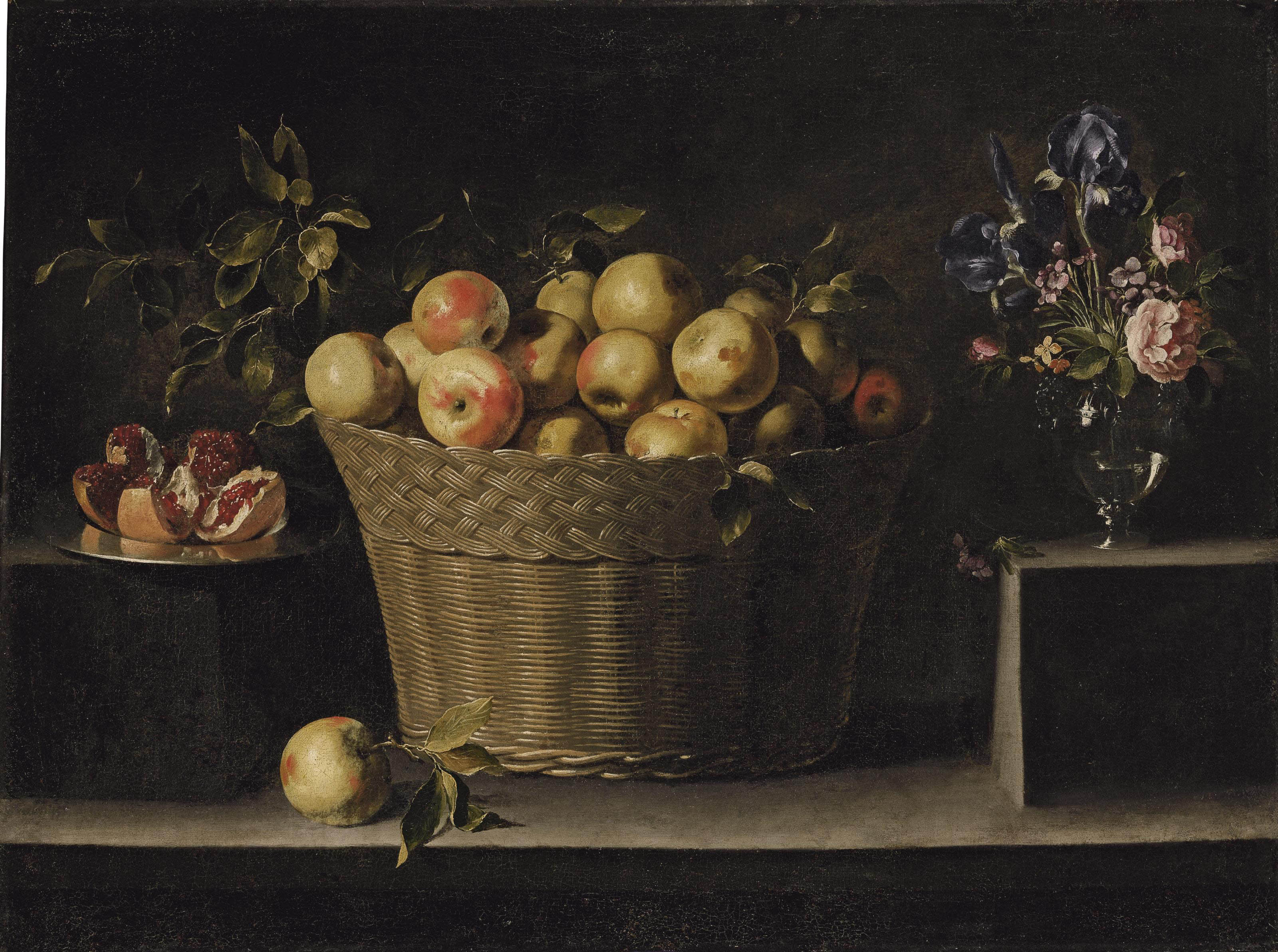 Apples in a wicker basket, an opened pomegranate on a silver plate and roses, irises and other flowers in a glass vase, on a stone ledge
