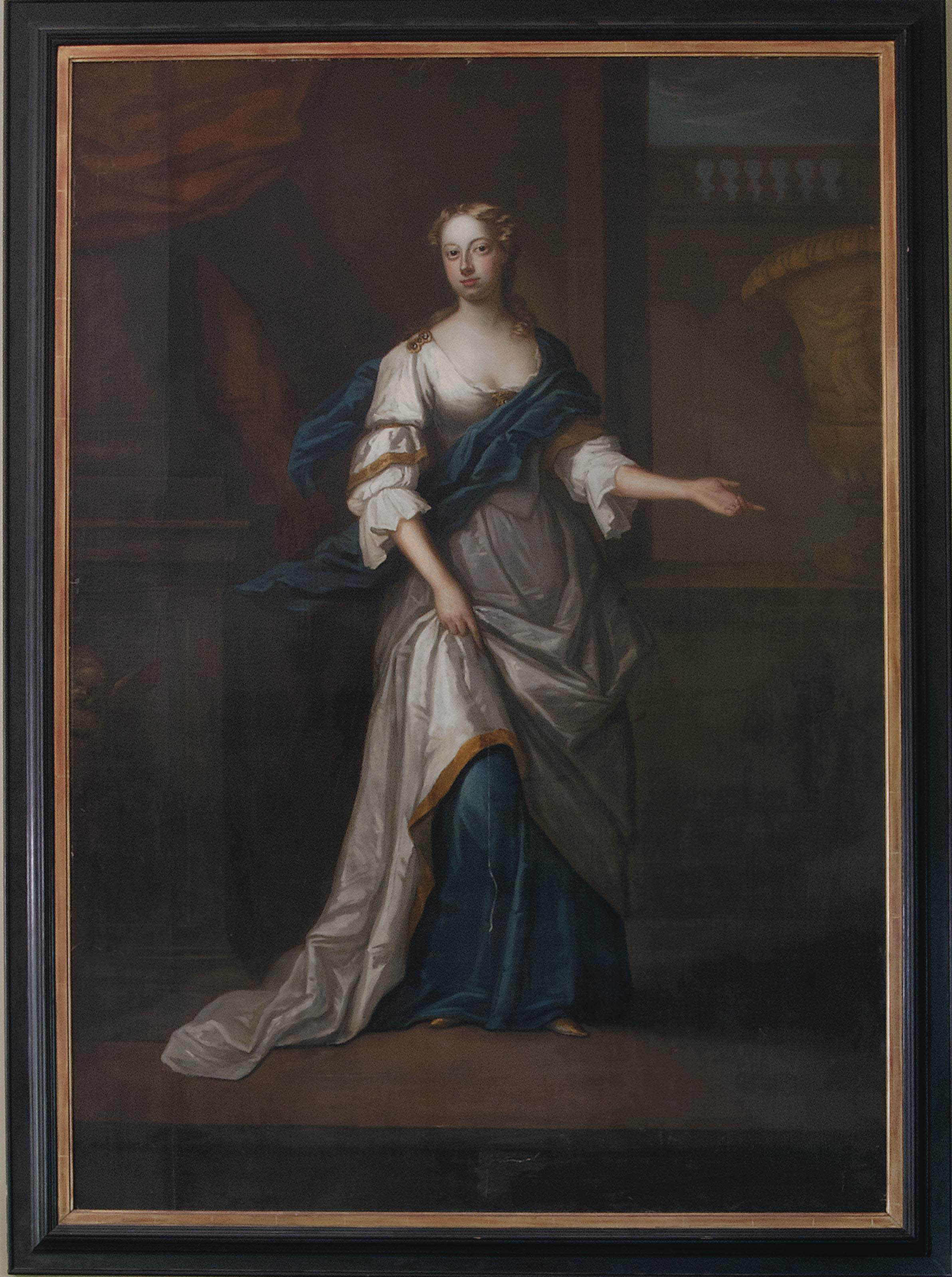 Portrait of a lady, full-length, in an oyster satin dress and blue wrap, standing beside a classical urn