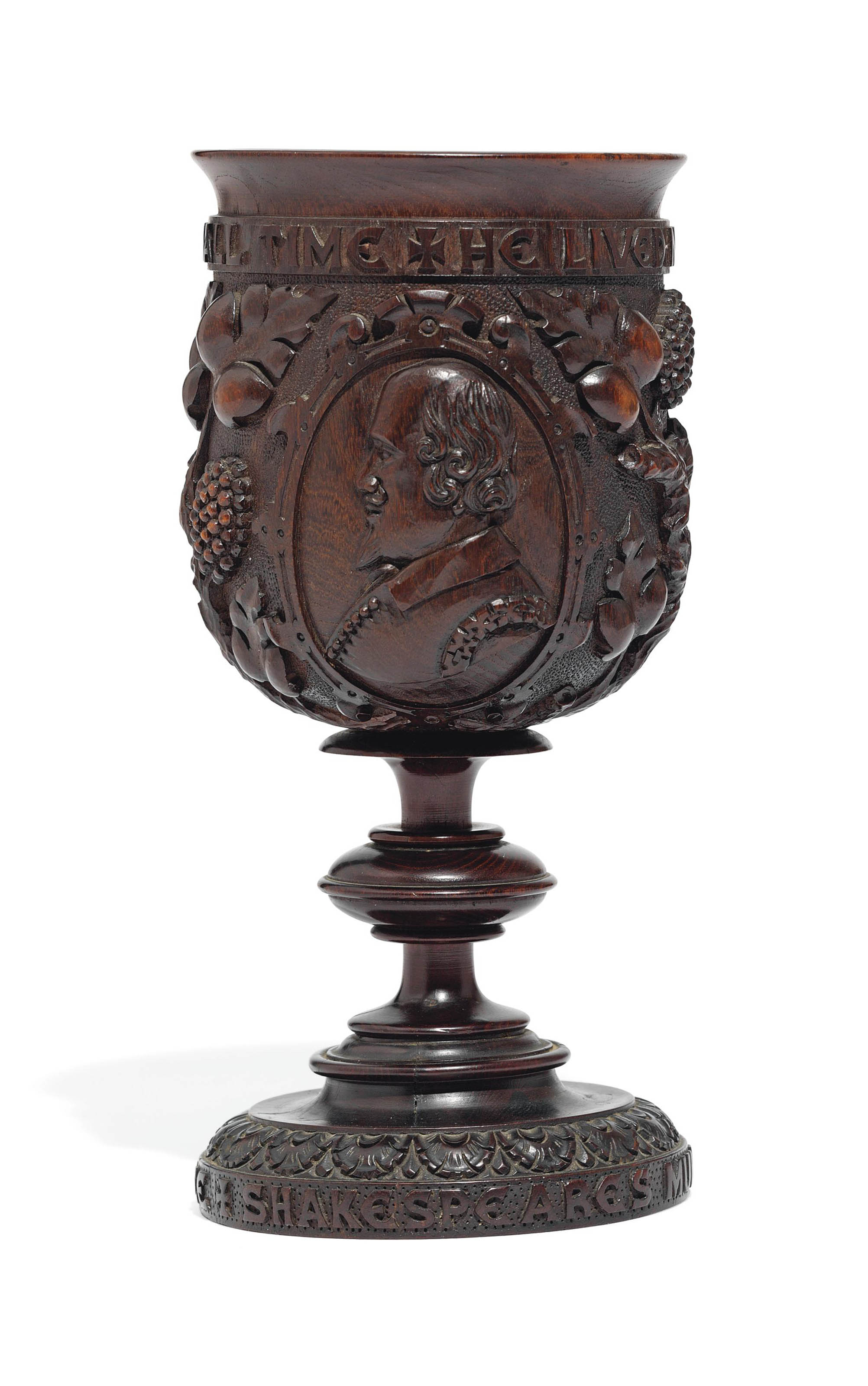 SHAKESPEARIANA -- An English mulberry goblet, [ca. 1864], by J[ohn] Marshall, the bowl with carved bust of Shakespeare in high relief, acorns, vines and Shakespeare's coat-of-arms, the upper rim carved with Ben Jonson's eulogy: 'He lived not for an age but for all time', and the lower rim: 'Shakespeare's Mulberry Wood from New Place', underside incised: 'J. Marshall Carver/Stratford on Avon' (superficial cracks at base), 224mm. high, 104mm. diameter.