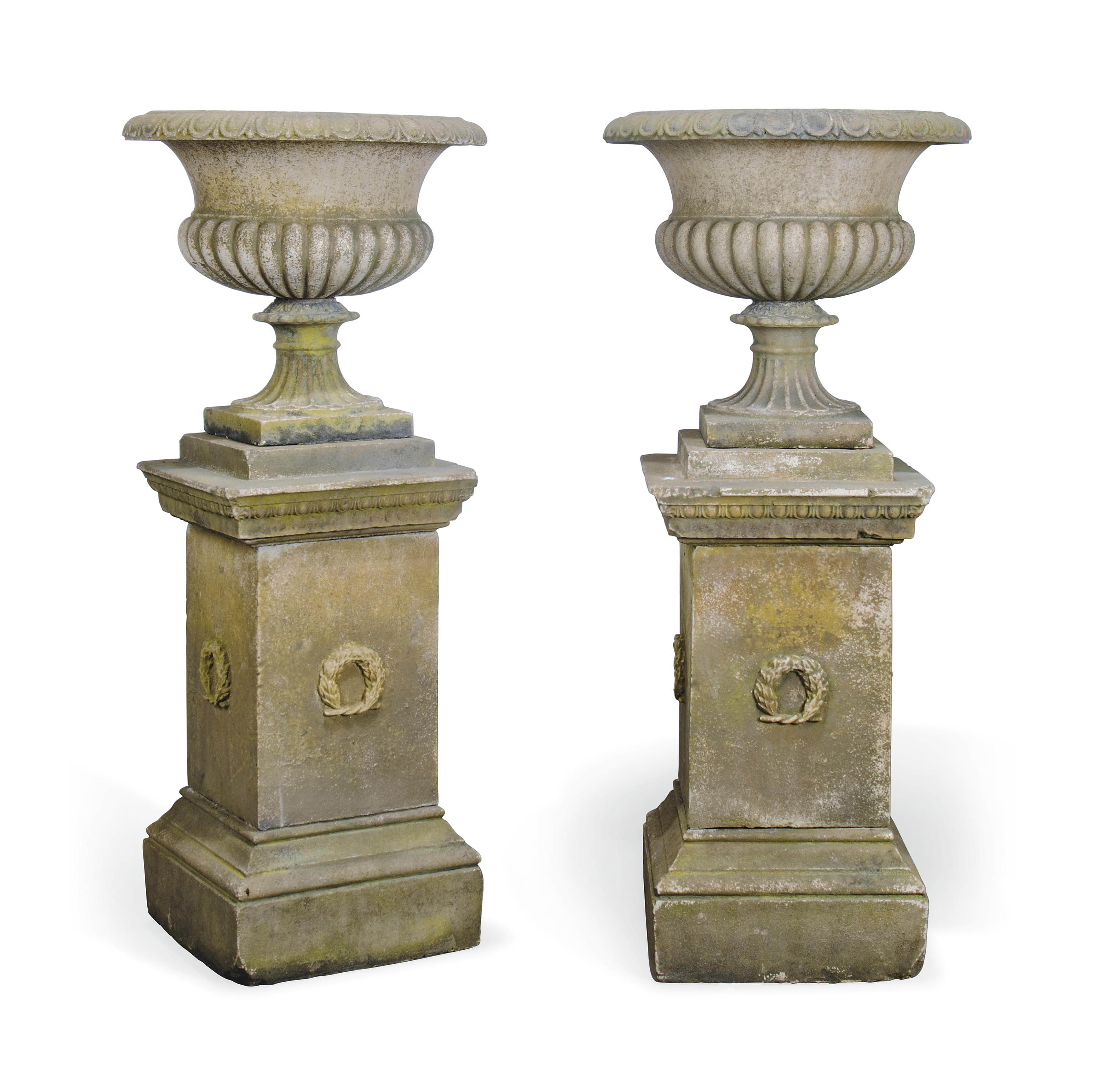 A PAIR OF COMPOSITE STONE GARDEN URNS ON PLINTHS OF RECENT
