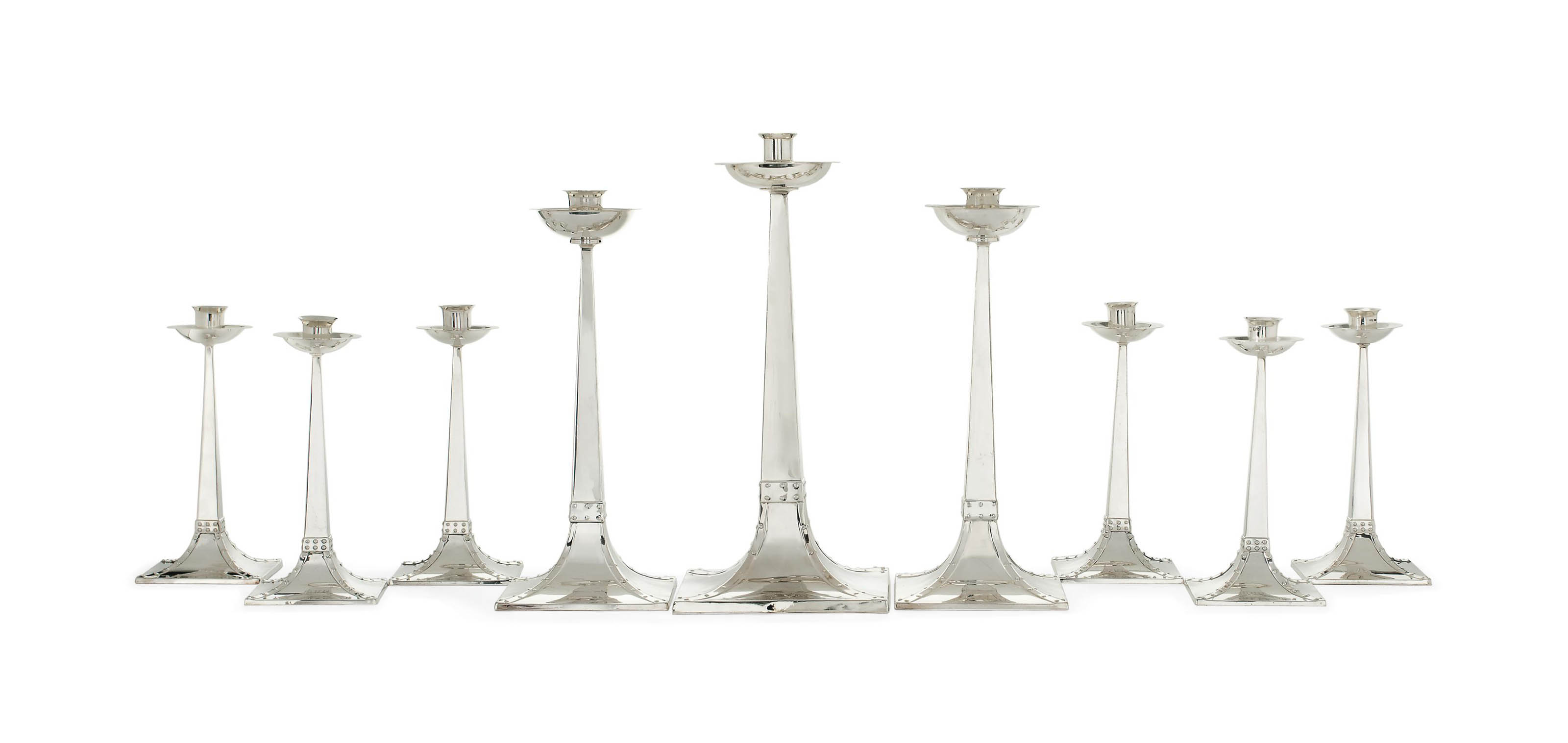 A GRADUATED AND MATCHED SET OF NINE ARTS & CRAFTS SILVER CANDLESTICKS BY JAMES DIXON & SON AND EDWARDS & CO