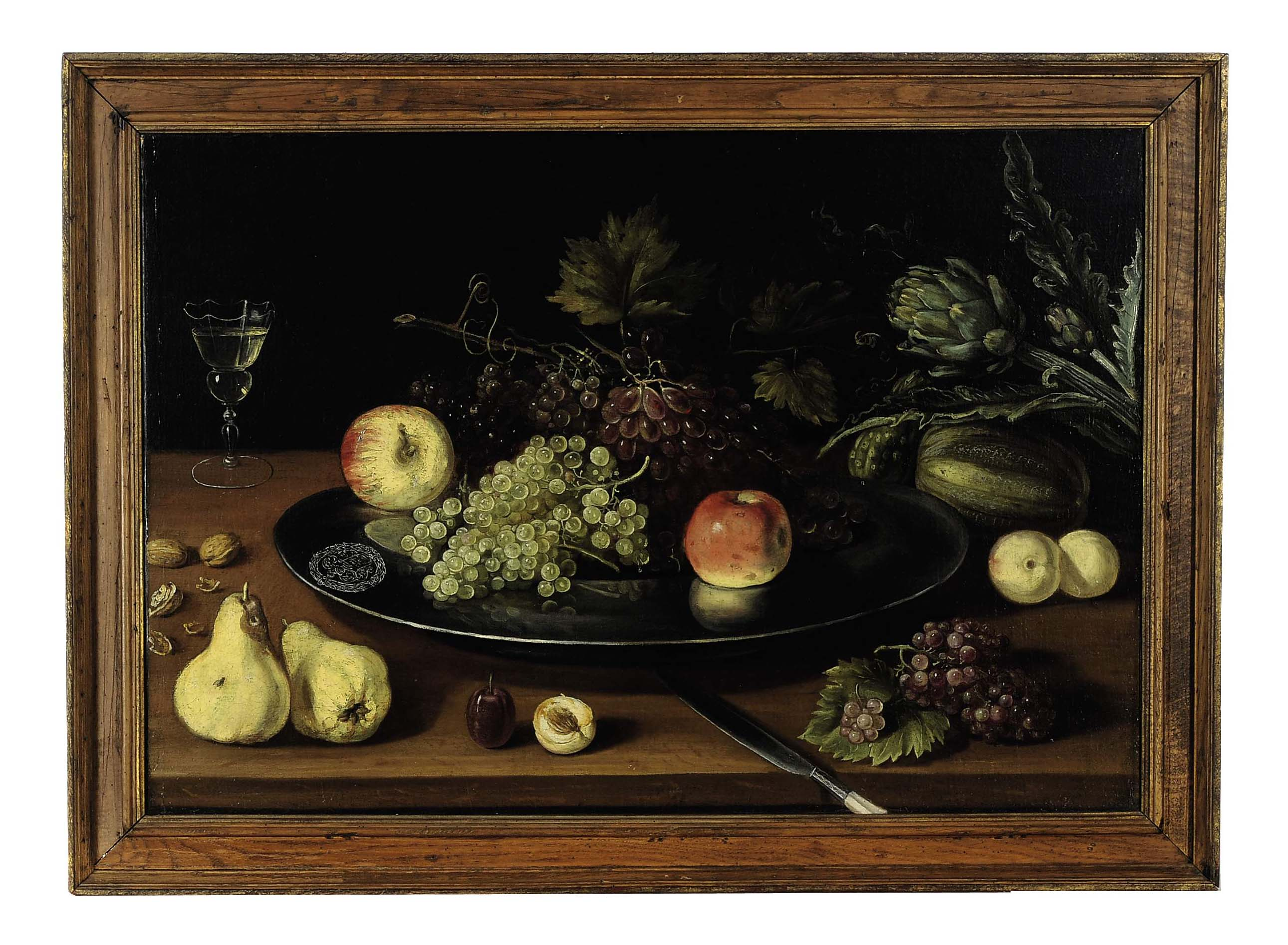 Still life of fruit, walnuts, artichokes and a glass of wine on a table