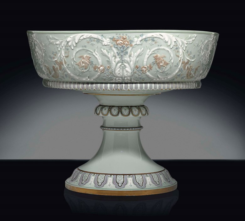 A Sèvres (hard paste) porcelain '1867 Paris Universelle Exposition' pâte-sur-pâte celadon-ground large footed bowl (coupe de rivoli, première grandeur). Twice stencilled green lozenge mark for 1864, iron-red crowned N Decore a Sèvres mark for 1864, potter's incised DG-57-3 for March 1857, the model designed by Jules Dieterle, the