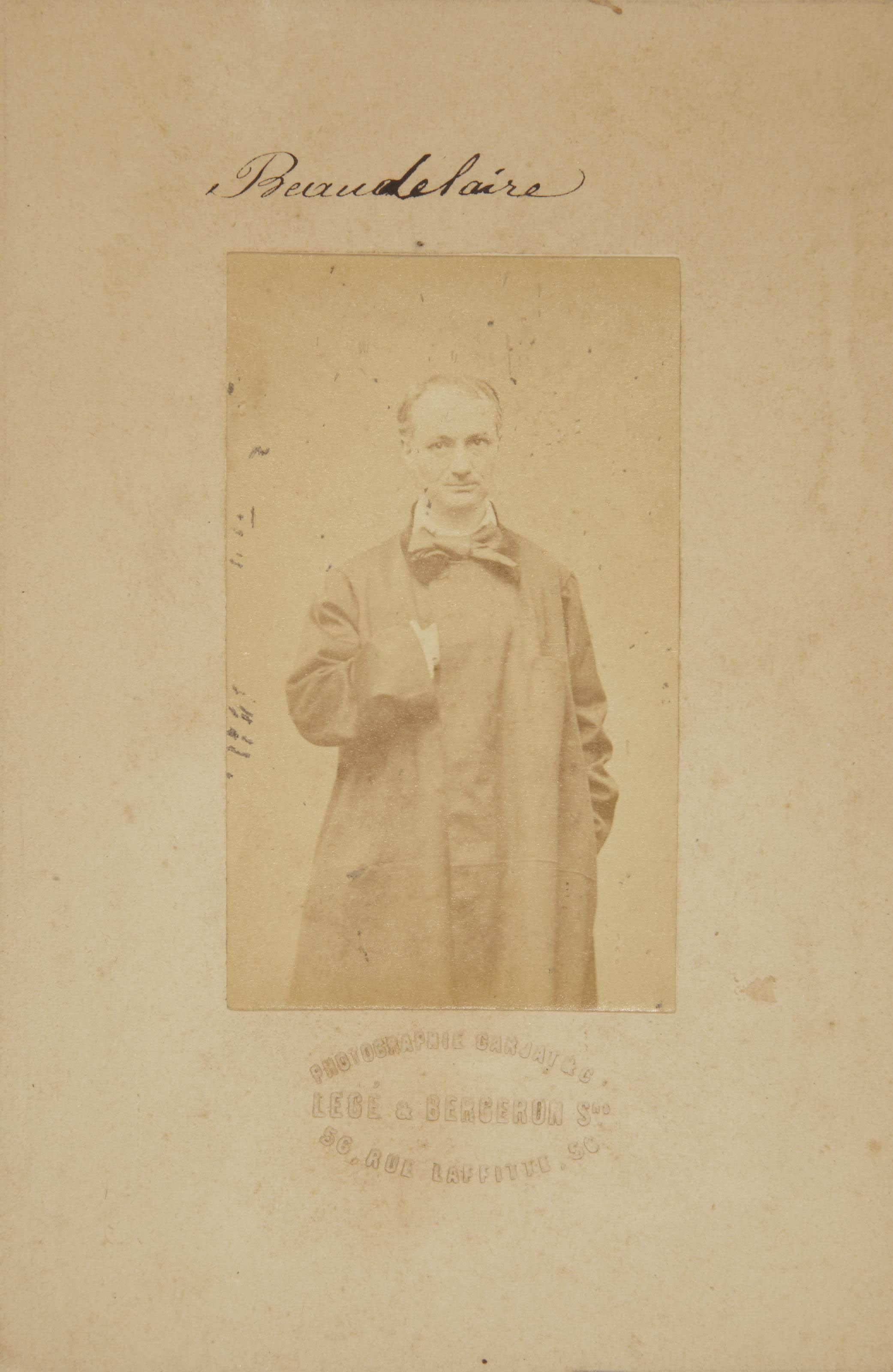 """[BAUDELAIRE] -- CARJAT, Étienne (1828-1906). Portrait carte-de-visite de Charles Baudelaire (91 x 54 mm) par Étienne Carjat, épreuve sur papier albuminé, avec son carton d'origine (image 9.2 x 5.2 cm.- 3 5/8 x 2 1/8 in.), portant l'inscription à la plume """"Beaudelaire"""" [sic] ainsi que le timbre sec sur le montage 'Photographie Carjat & Cie  Legé & Bergeron Srs  56, Rue Lafitte, 56.' (Portrait avec petites taches d'encre et détaché, carton avec usures.)"""