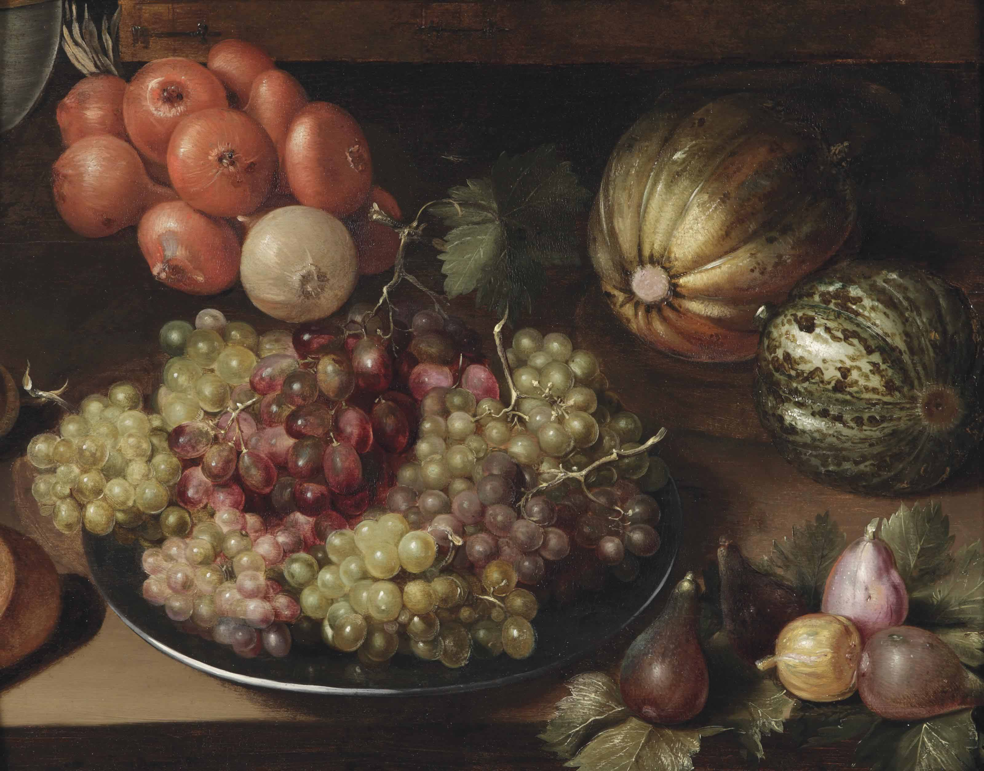 White and red grapes on a pewter plate, a string of onions, two melons and figs, all on a wooden table