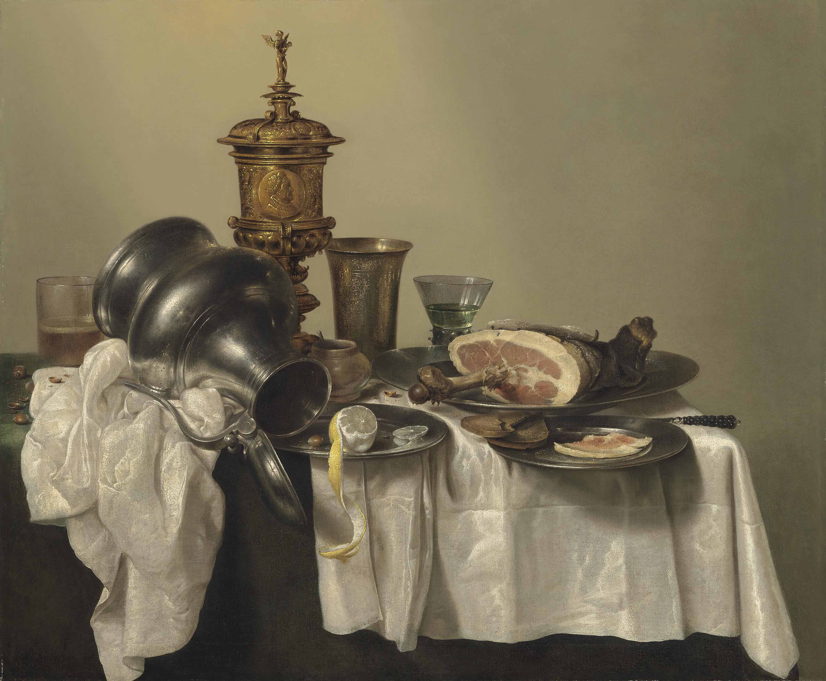 A leg of ham, a partly-peeled lemon and slices of bread on pewter platters, a berkemeier, an upturned tankard, a silver-gilt cup and cover, and other vessels on a partly-draped table
