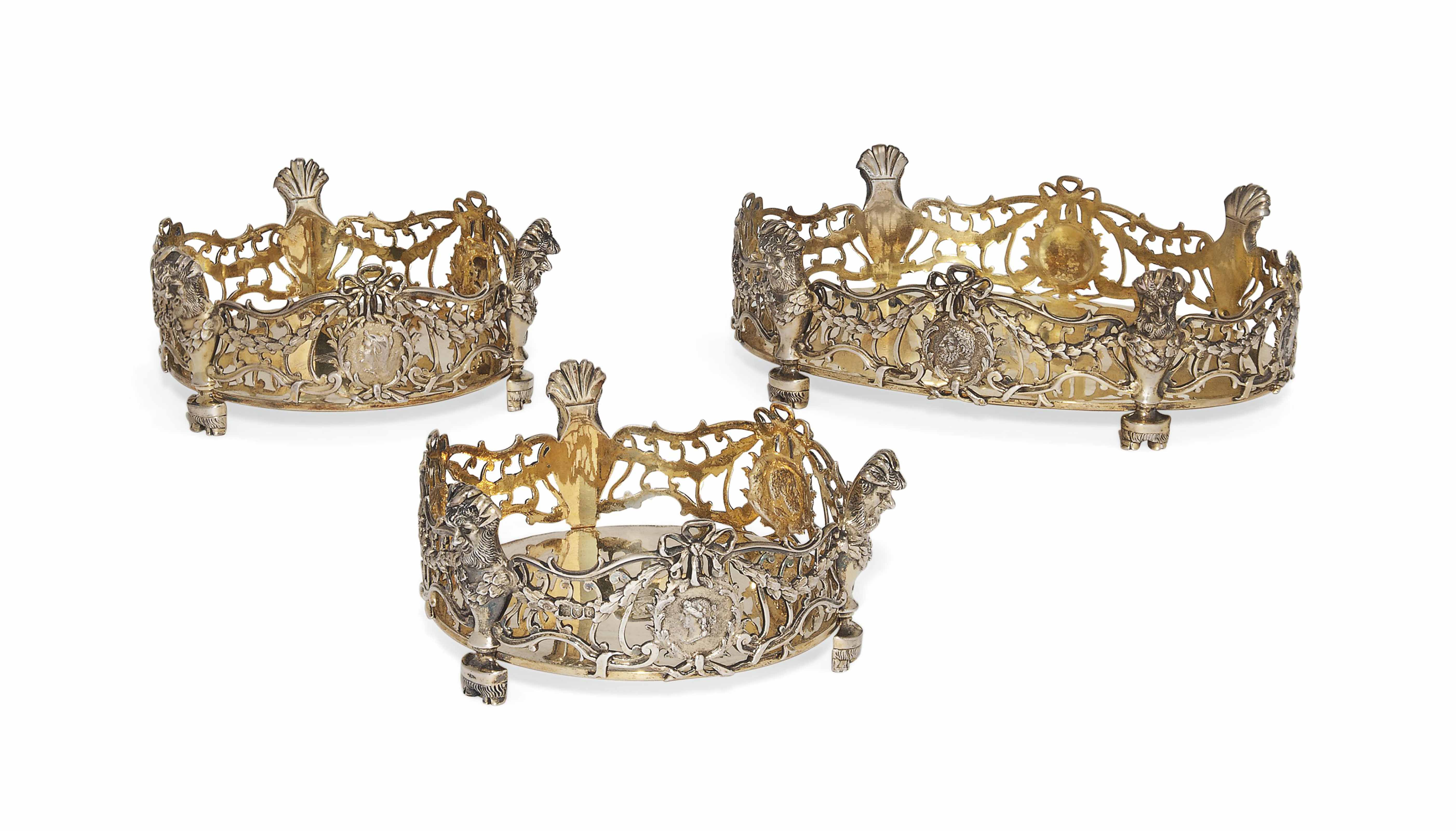 A SUITE OF THREE LATE VICTORIAN SILVER-GILT COASTERS IN 18TH CENTURY DUTCH STYLE