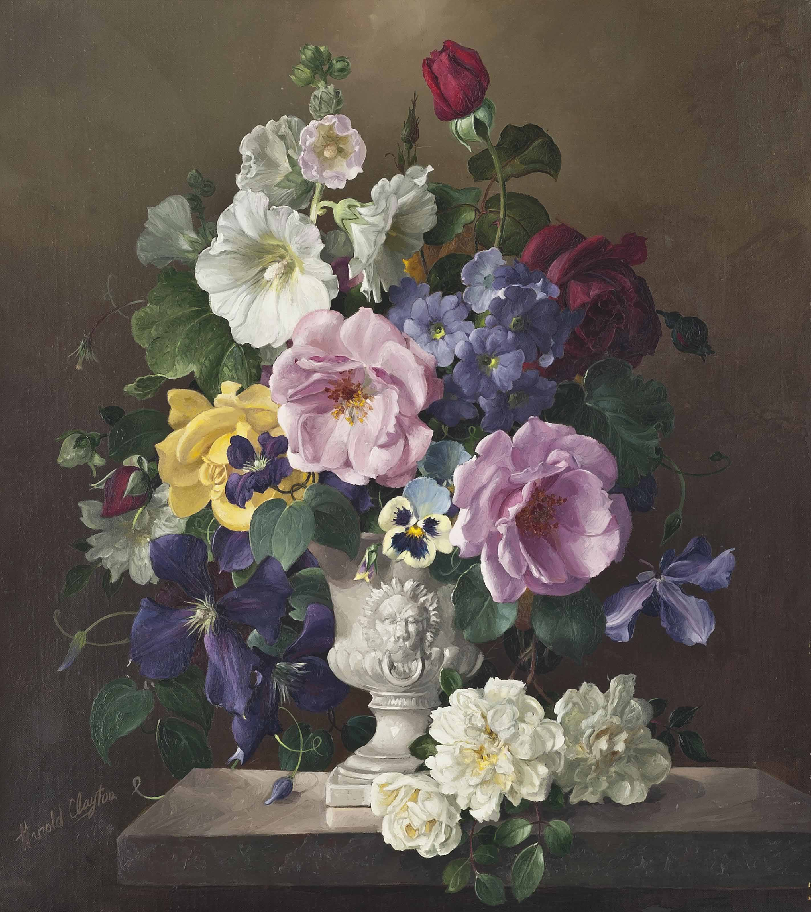 Roses, clematis, lavatera, and pansies in an urn