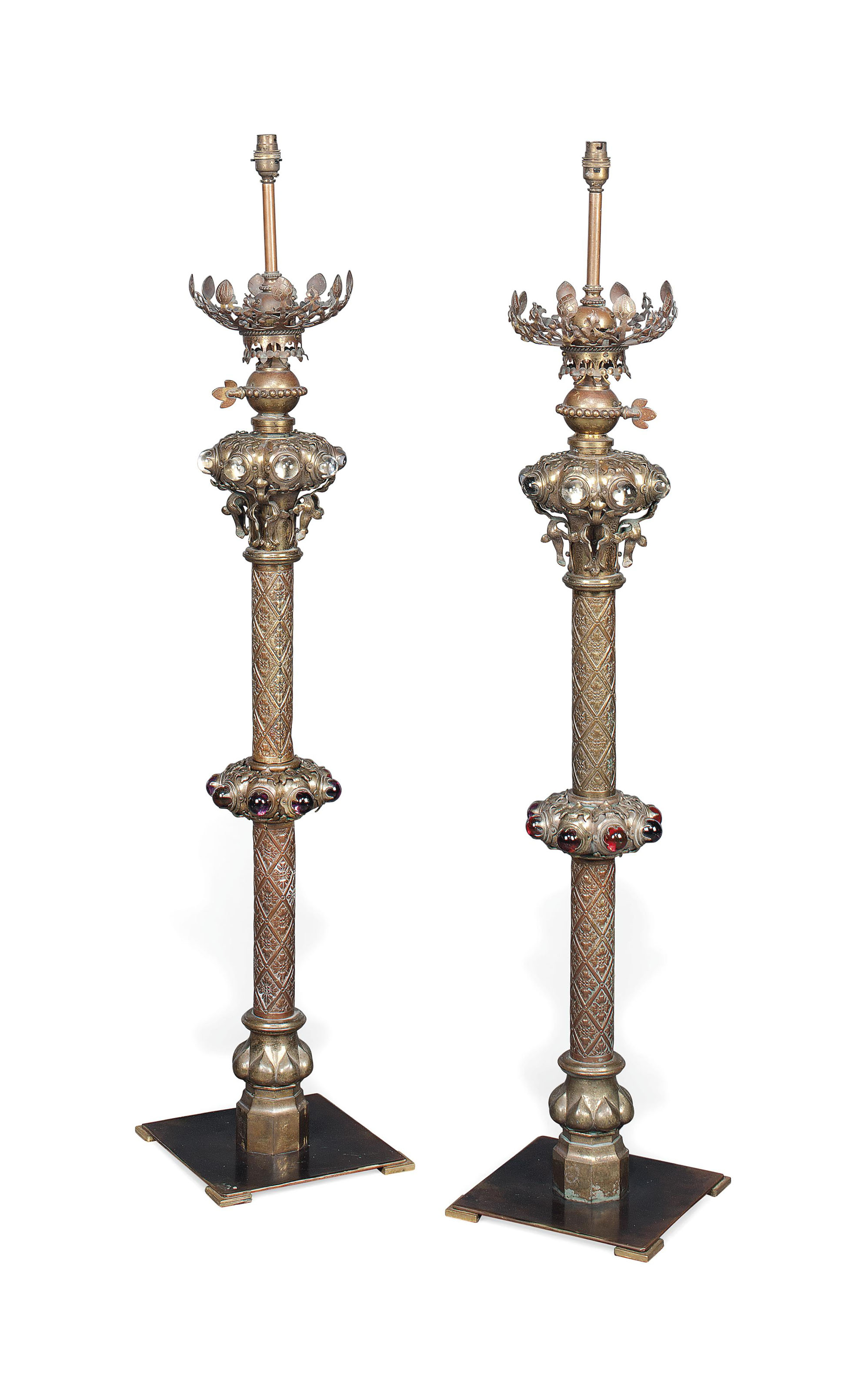 A PAIR OF VICTORIAN GOTHIC BRASS CANDLESTICKS AS LAMPS
