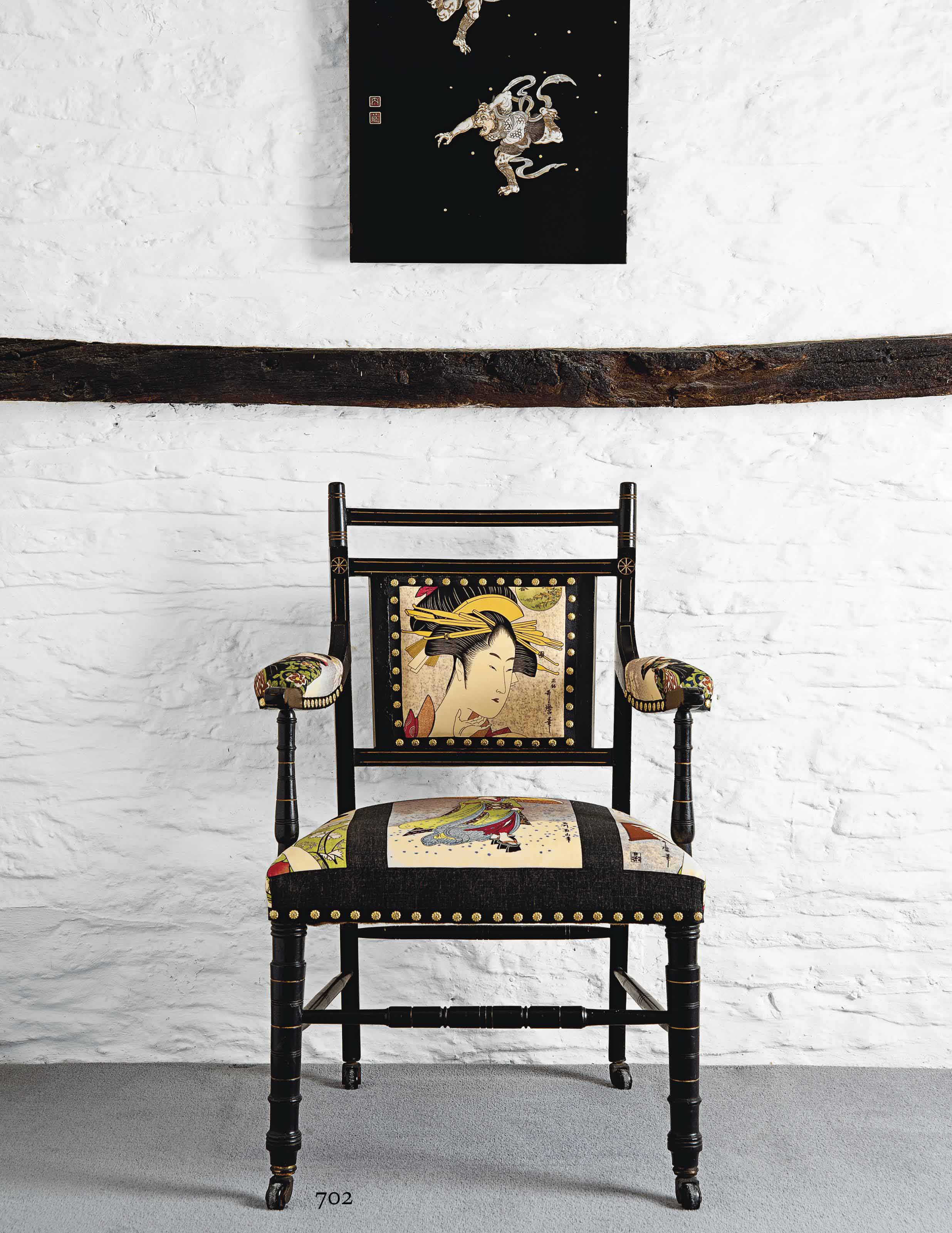 AN EBONISED WOOD AND UPHOLSTERED OPEN-ARMCHAIR MADE BY OETZMANN, AFTER E.W. GODWIN (1833-1886)