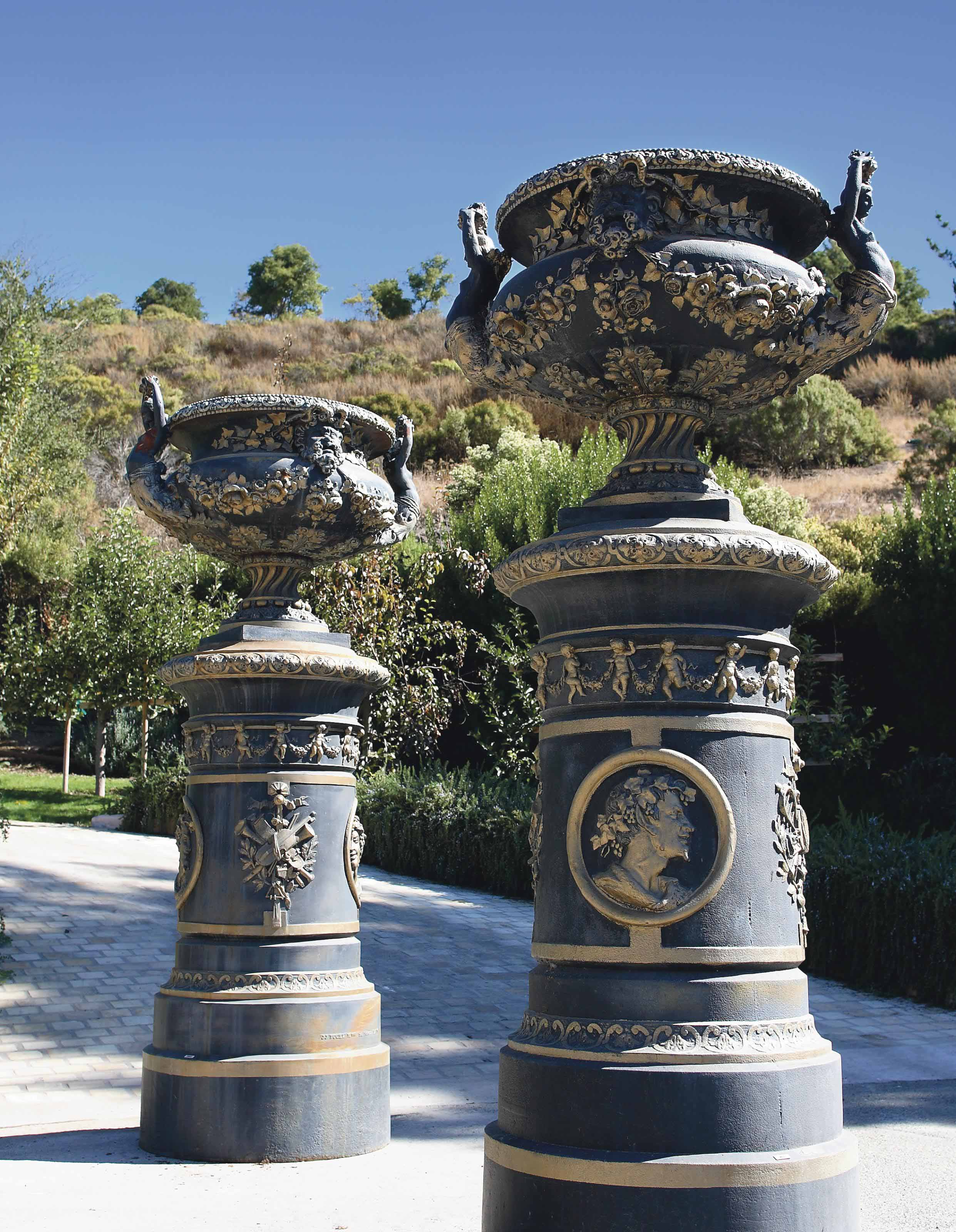A LARGE PAIR OF FRENCH PARCEL-GILT AND BLACK-PAINTED CAST-IRON URNS ON PEDESTALS