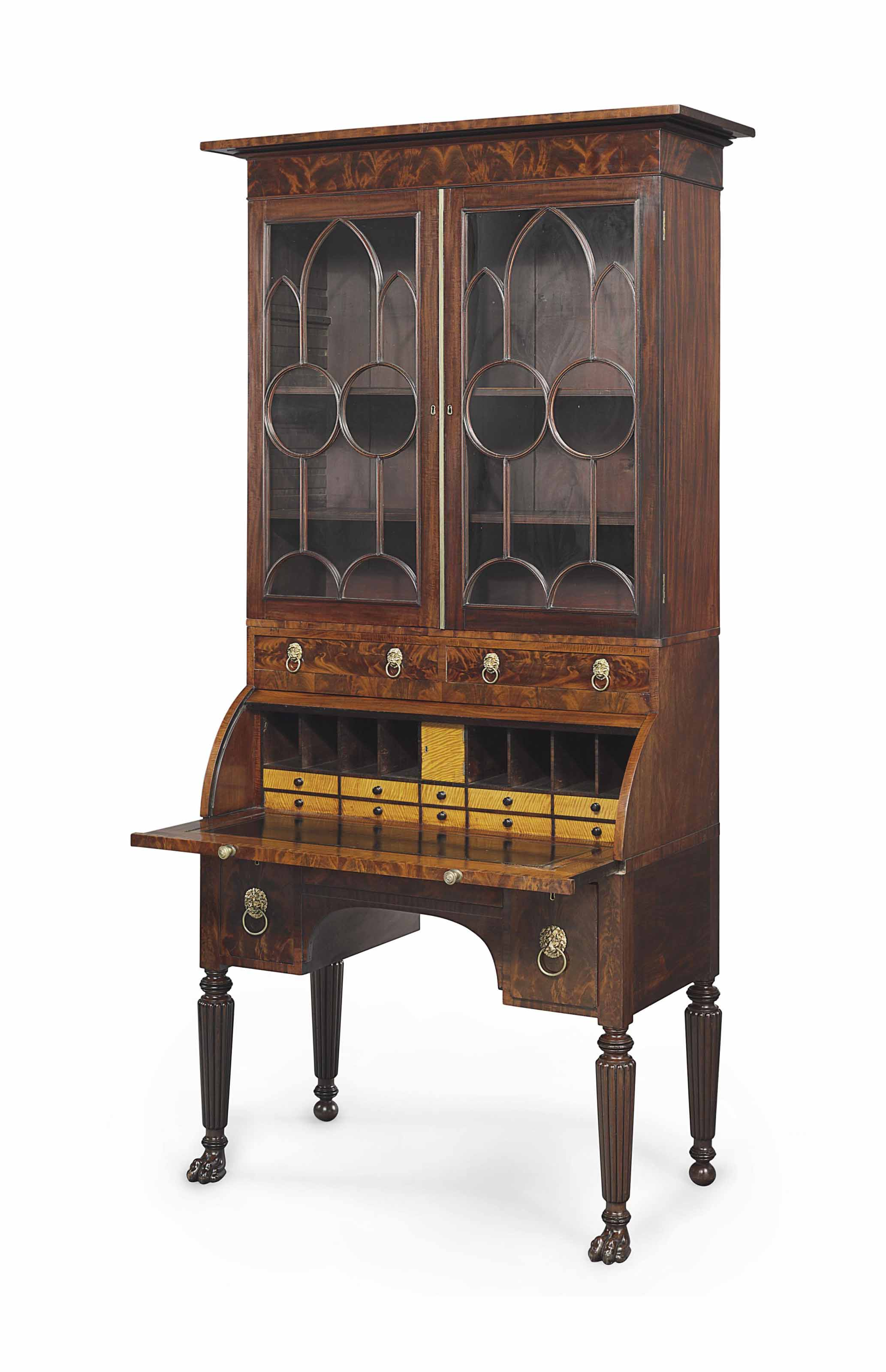 A CLASSICAL CARVED AND FIGURED MAHOGANY CYLINDER-FRONT DESK-AND-BOOKCASE