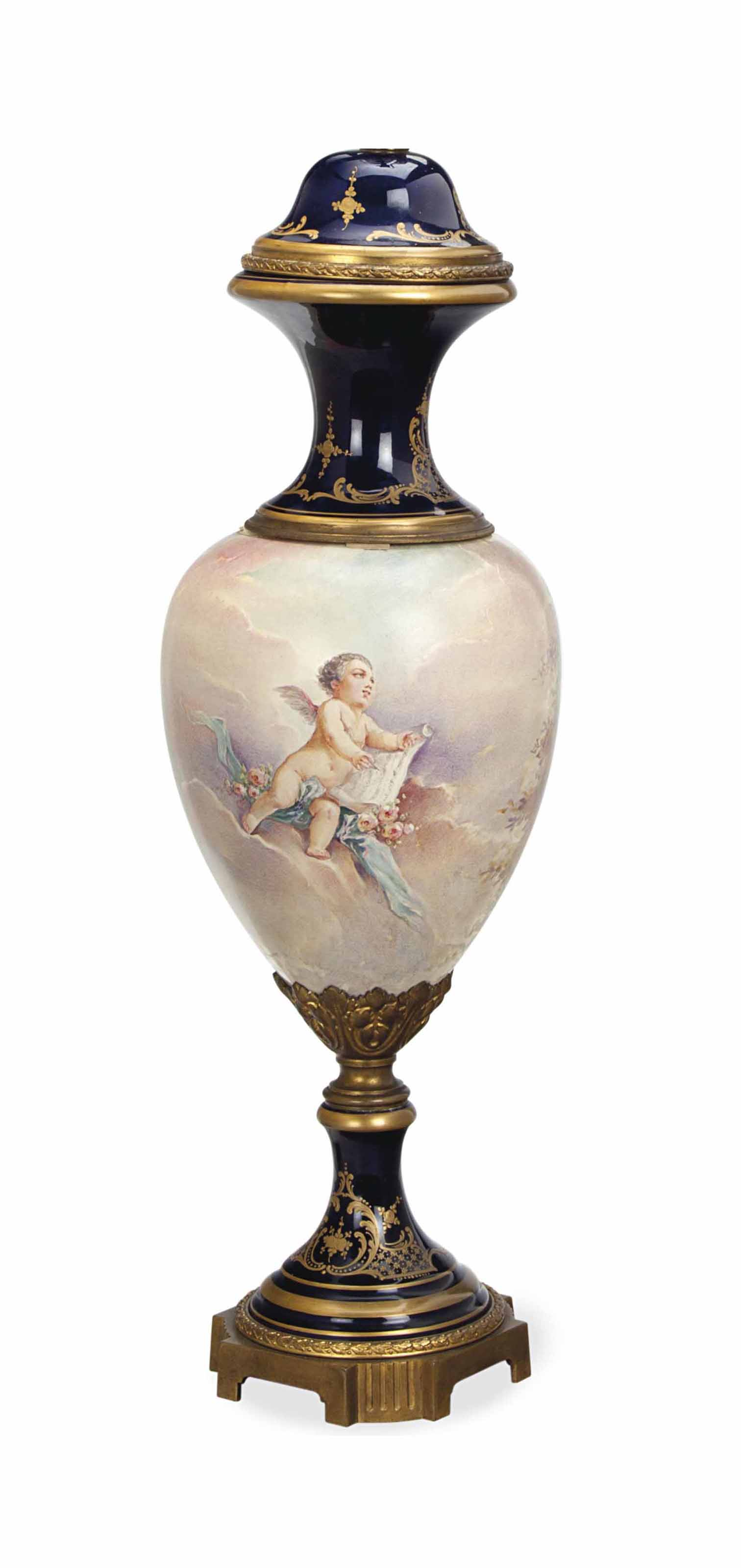 A GILT METAL MOUNTED SEVRES-STYLE PORCELAIN COBALT GROUND URN AND COVER, MOUNTED AS A LAMP,
