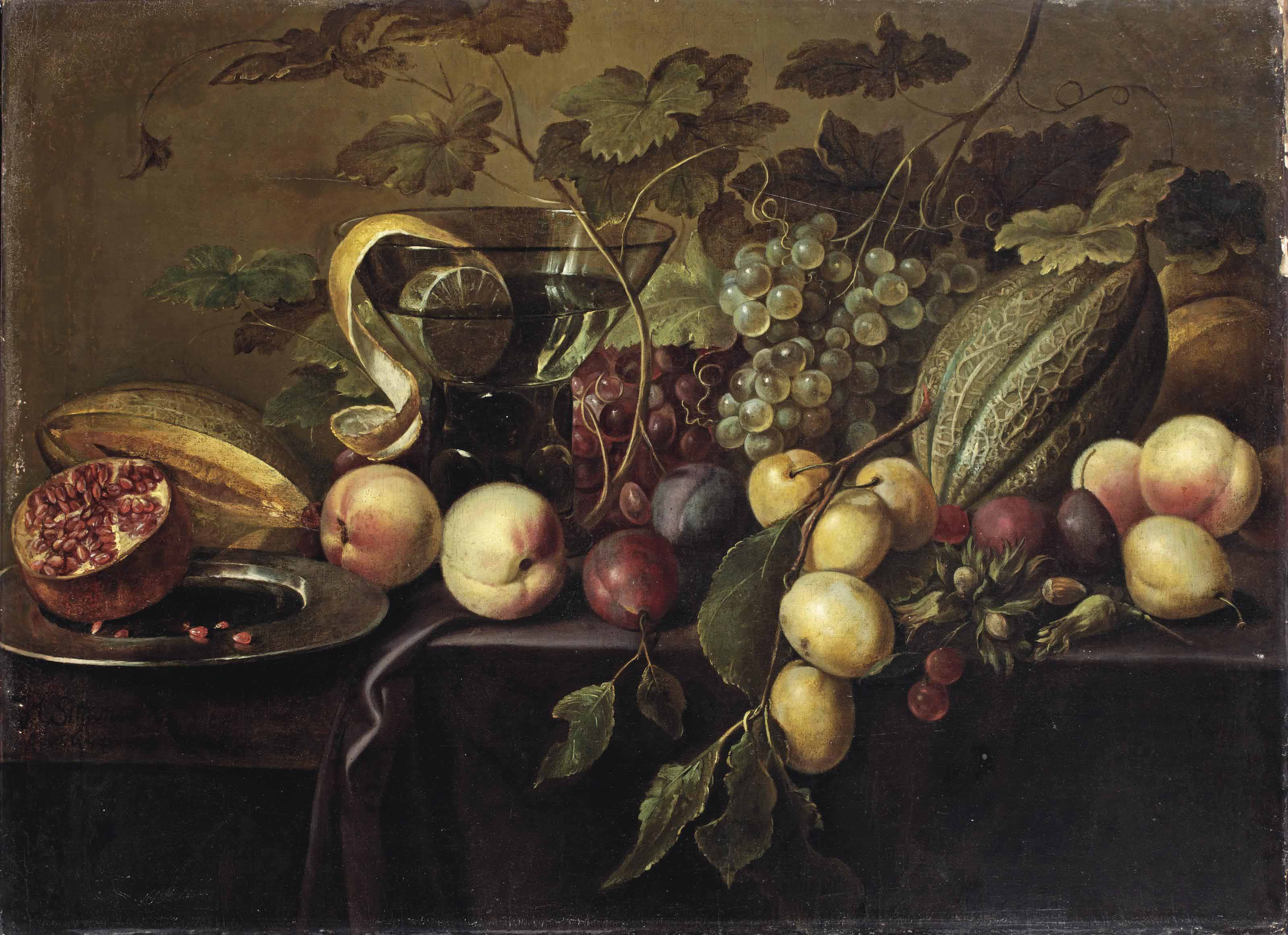 Plums, peaches, grapes, melons, a half pomegranate, and a peeled lemon in a glass, all on a partially draped table