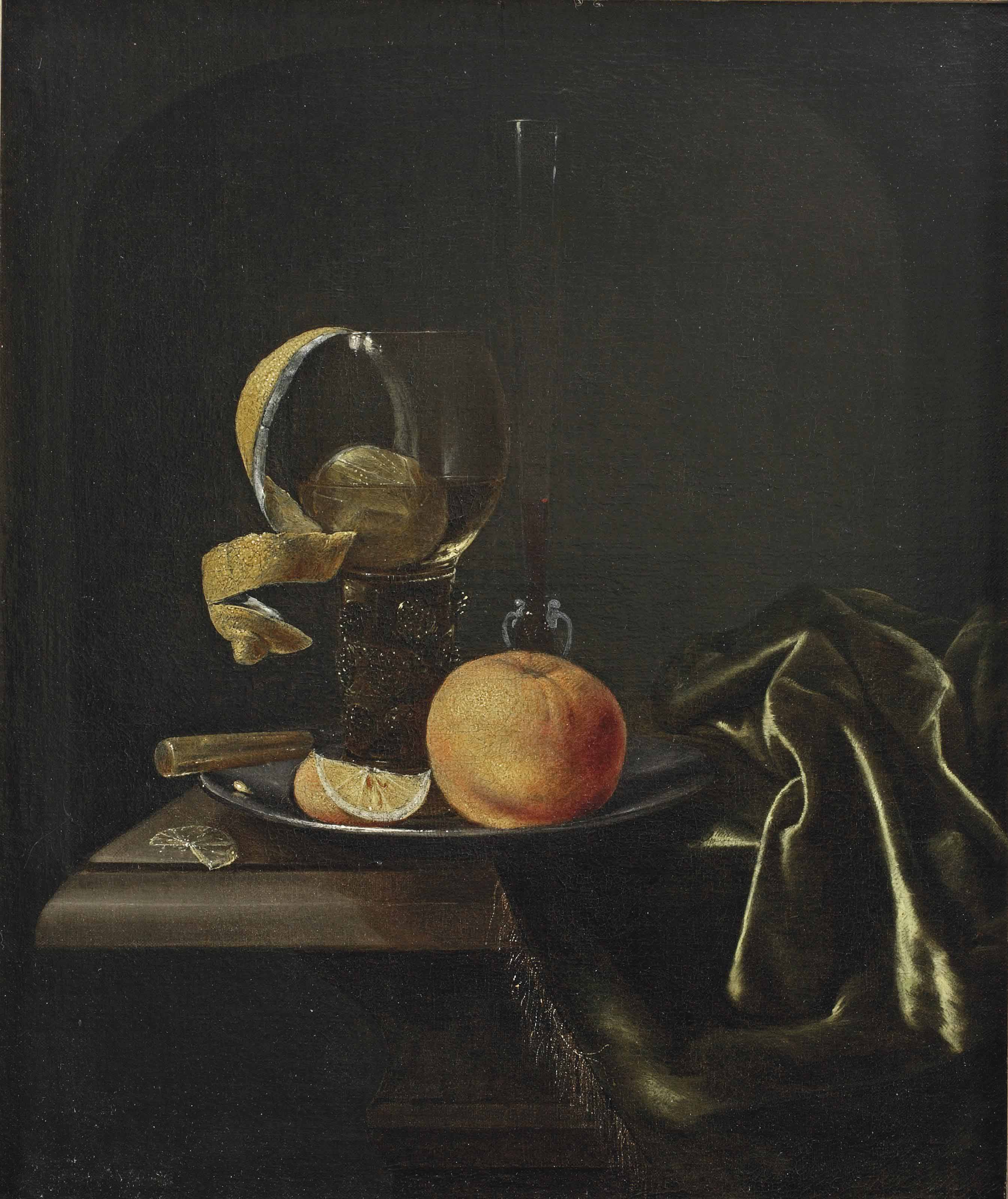 An orange, a peeled lemon and a glass on a pewter dish, all on a partially draped table