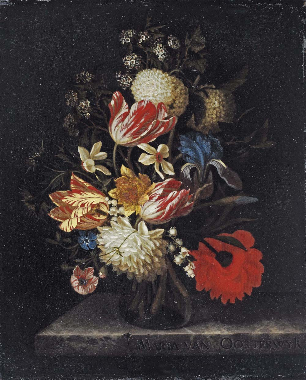 Tulips, lilies, roses, an iris and other flowers in a glass vase, on a marble ledge
