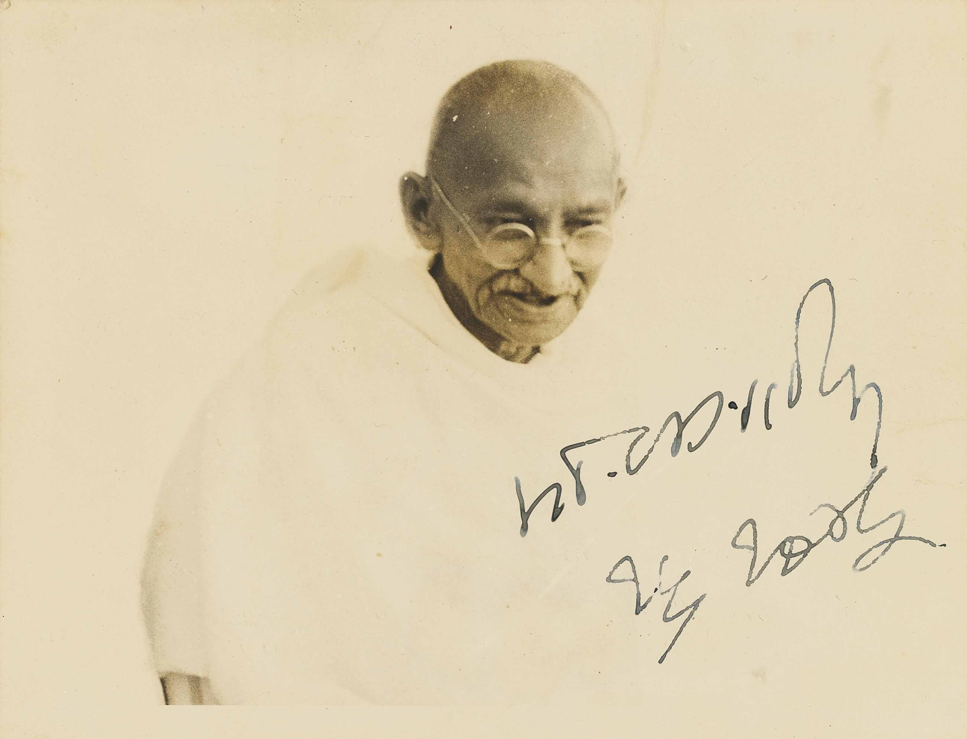 GANDHI, Mohandas Karamchand (1869-1948). Portrait photograph signed (on the image, in Devanagari script, 'M.K. Gandhi') and indistinctly dated ?1 June 1922 (or 23), 89 x 115mm (surface slightly scratched).