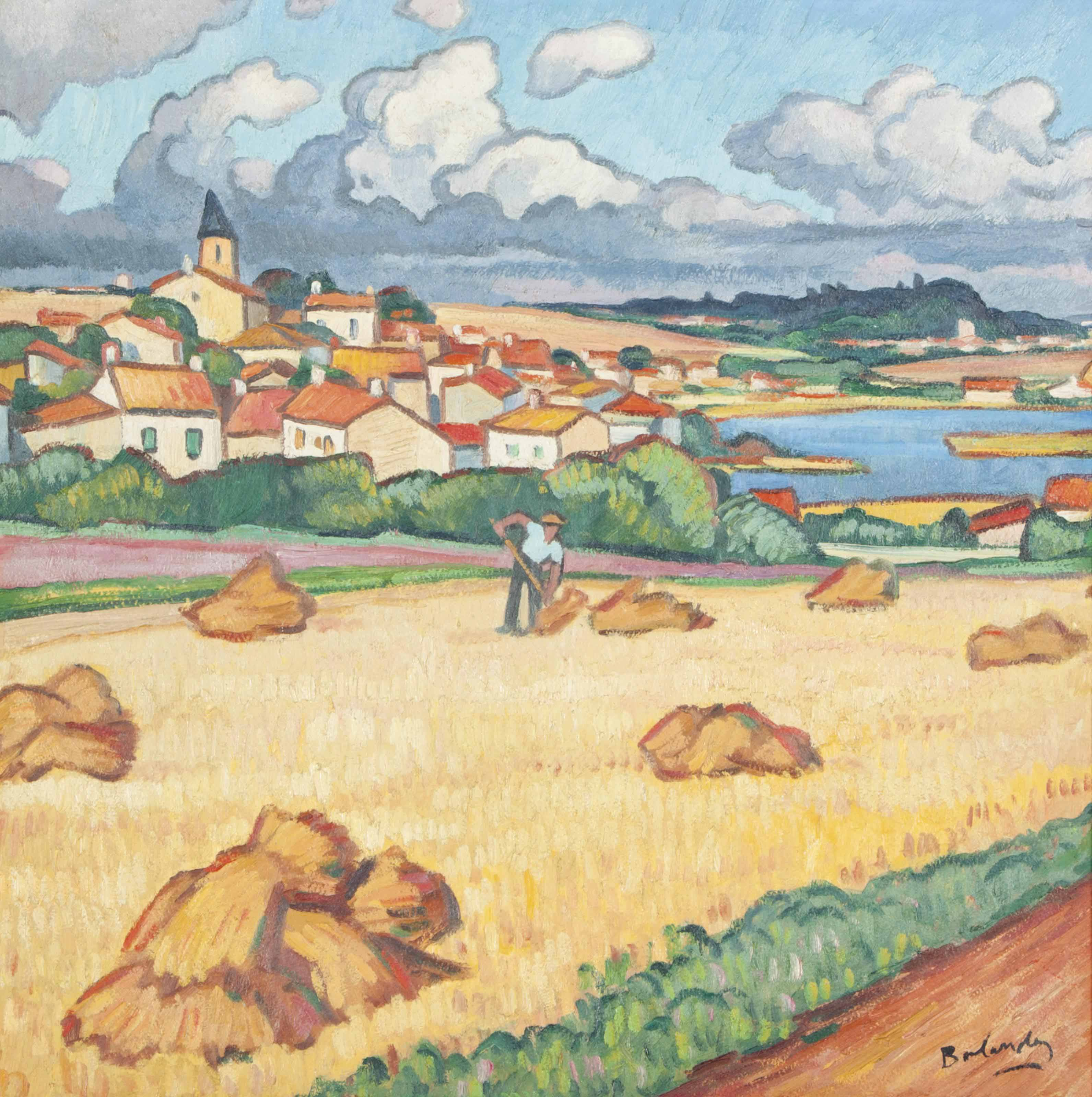 Worker in a field with a town in the background
