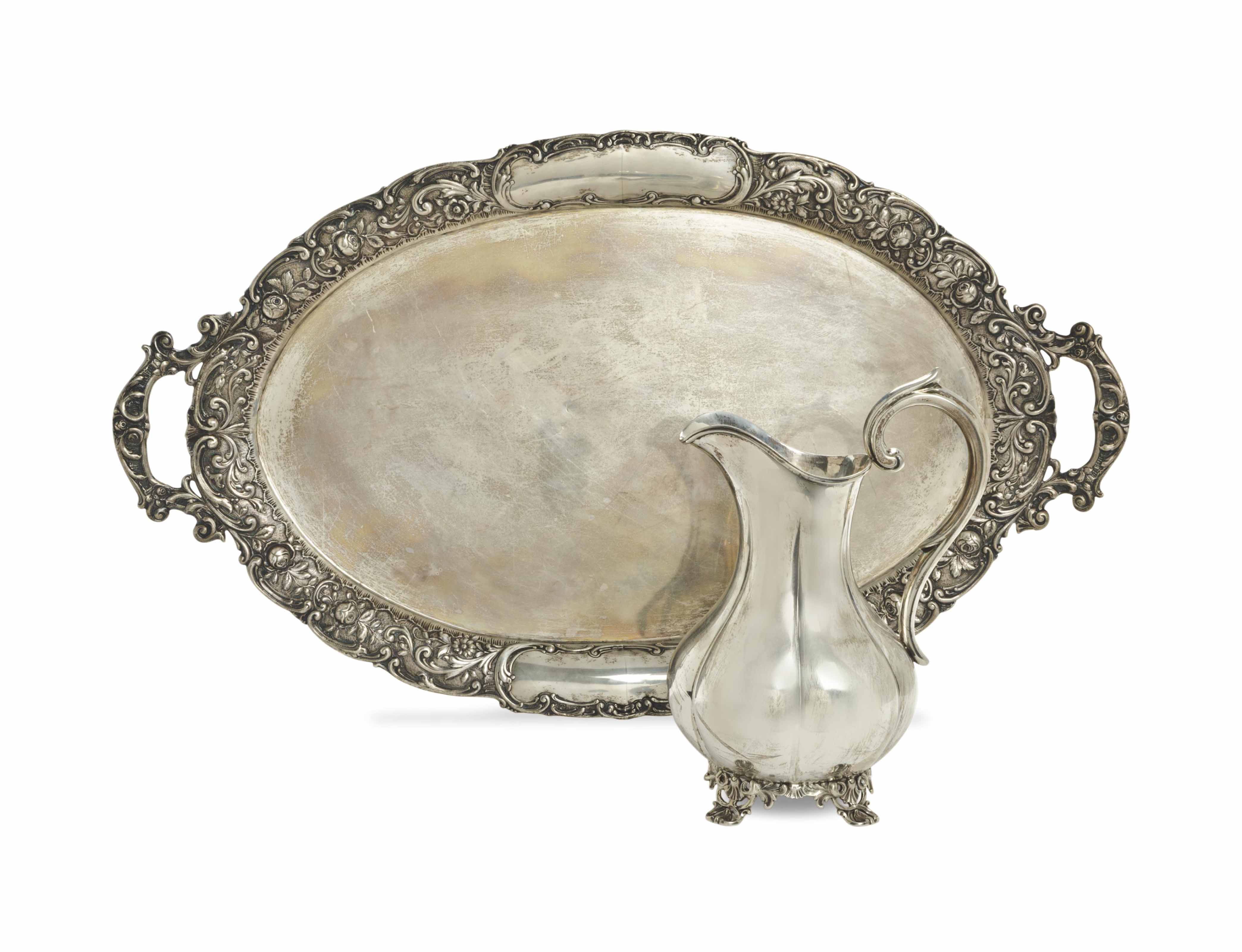 AN EARLY AMERICAN SILVER SHAPED WATER PITCHER, AND AN OVAL TWO HANDLED TRAY,